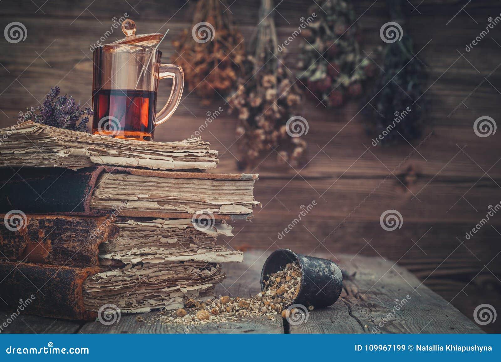 Kop van gezonde thee, mortier van kruiden en oude boeken Hangende bossen van geneeskrachtige kruiden op achtergrond