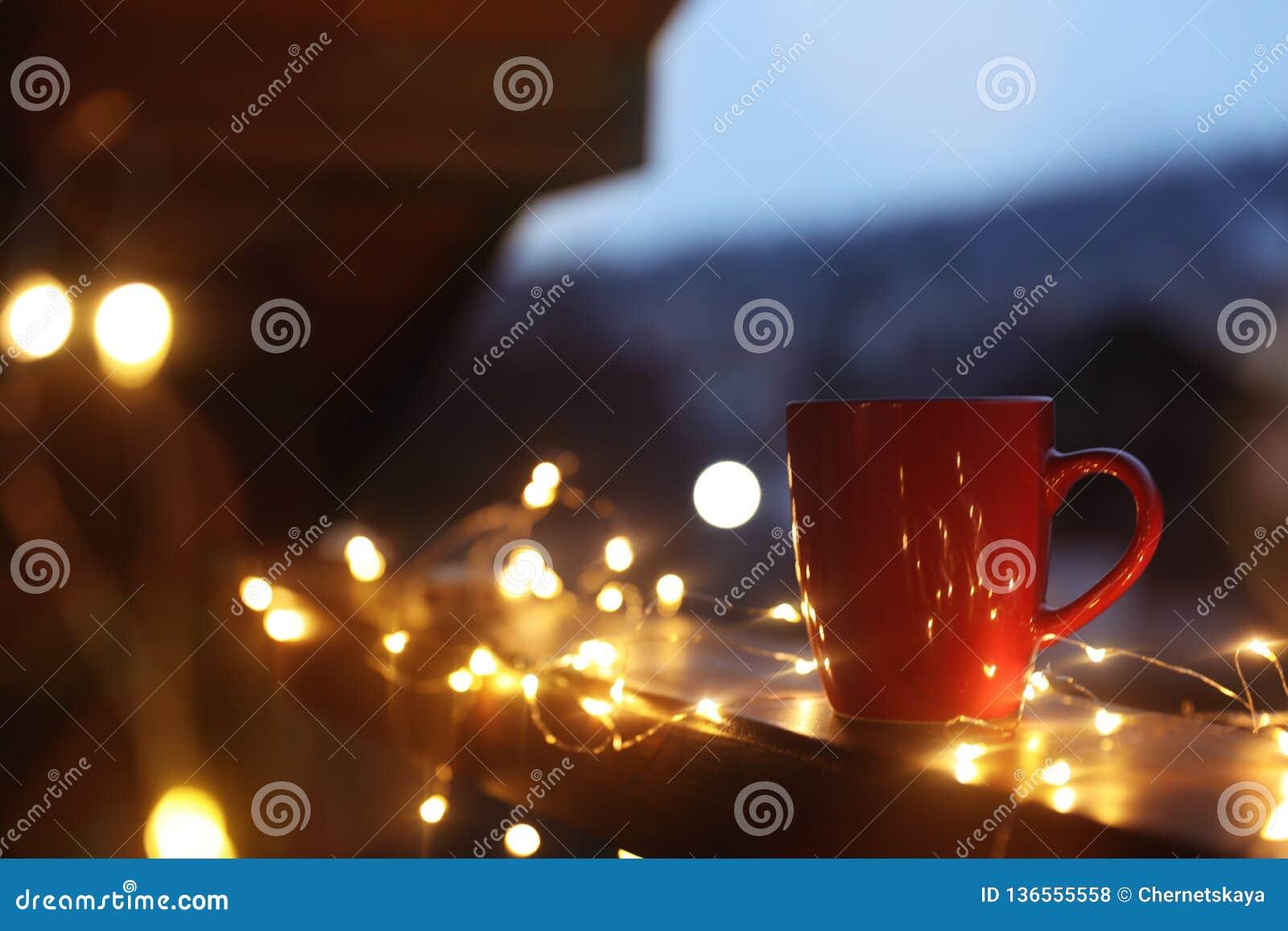 Kop van hete die drank op balkontraliewerk met Kerstmislichten wordt verfraaid, ruimte voor tekst De winter