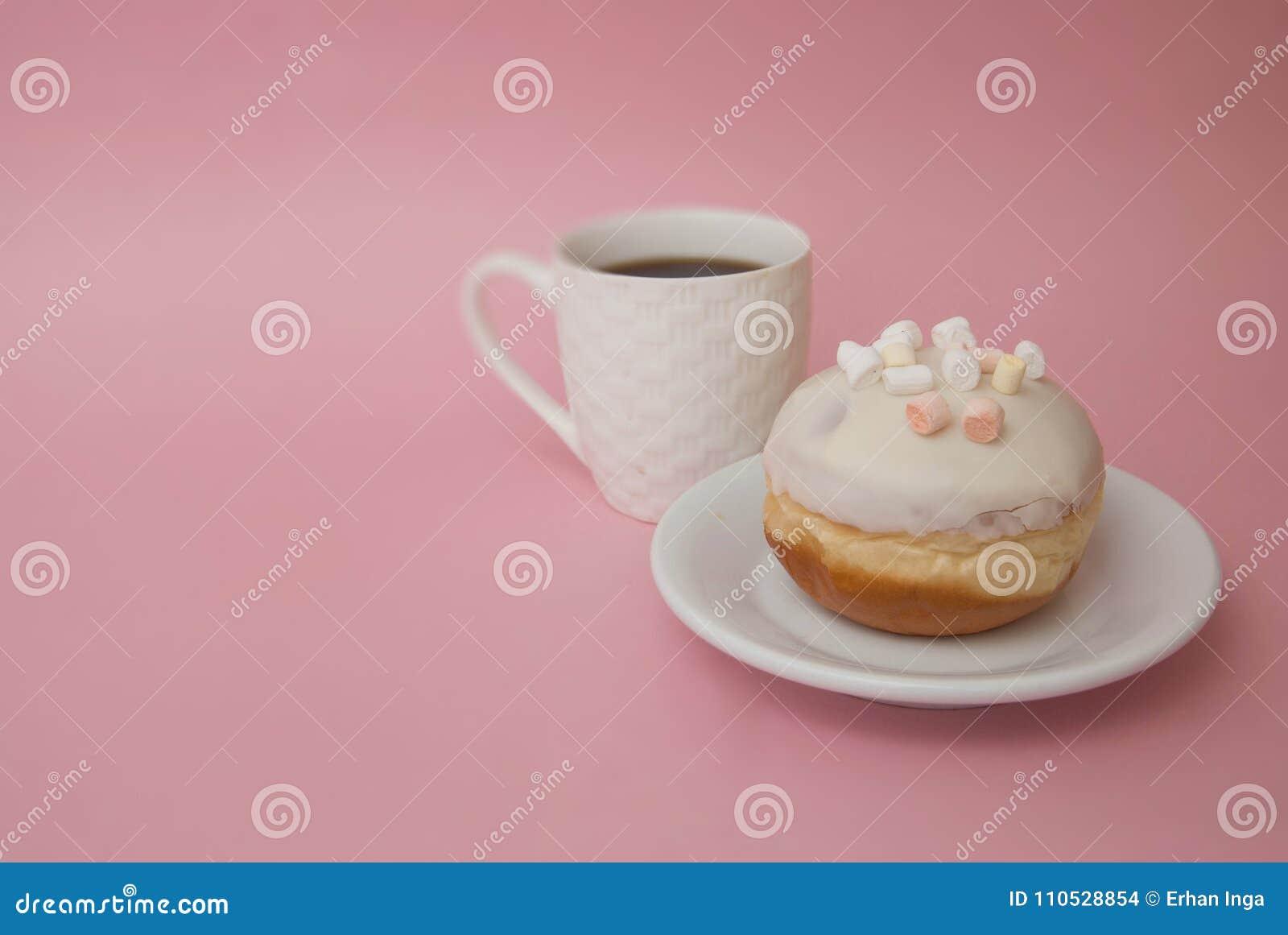 Kop van koffie en een Dessert Doughnuts met Wit Suikerglazuur op Witte Plaat over Pastelkleur Roze Achtergrond Zoet Dessert Donut
