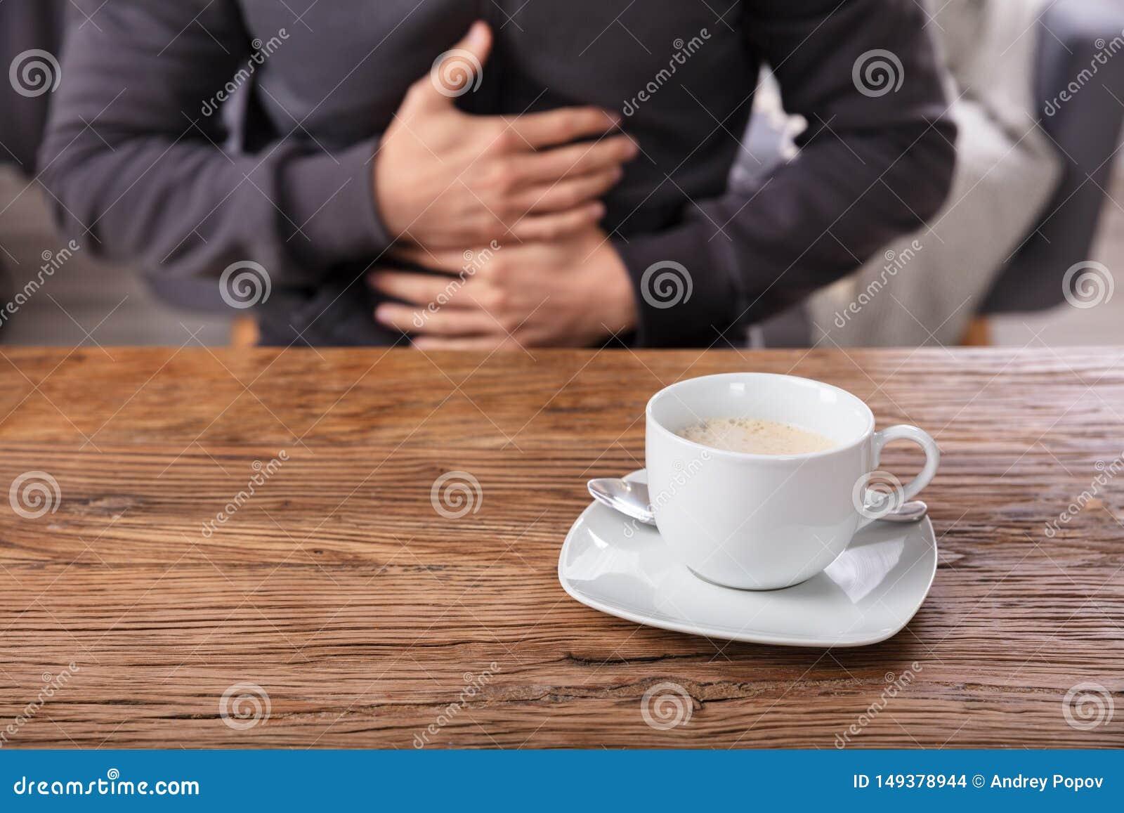 Kop van Koffie in Front Of Man Having Stomach-Pijn