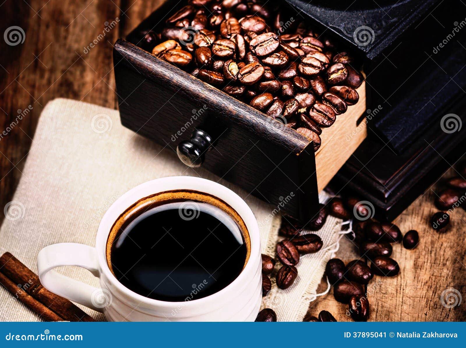 Kop van koffie met koffiebonen en Koffiemolen op houten bro
