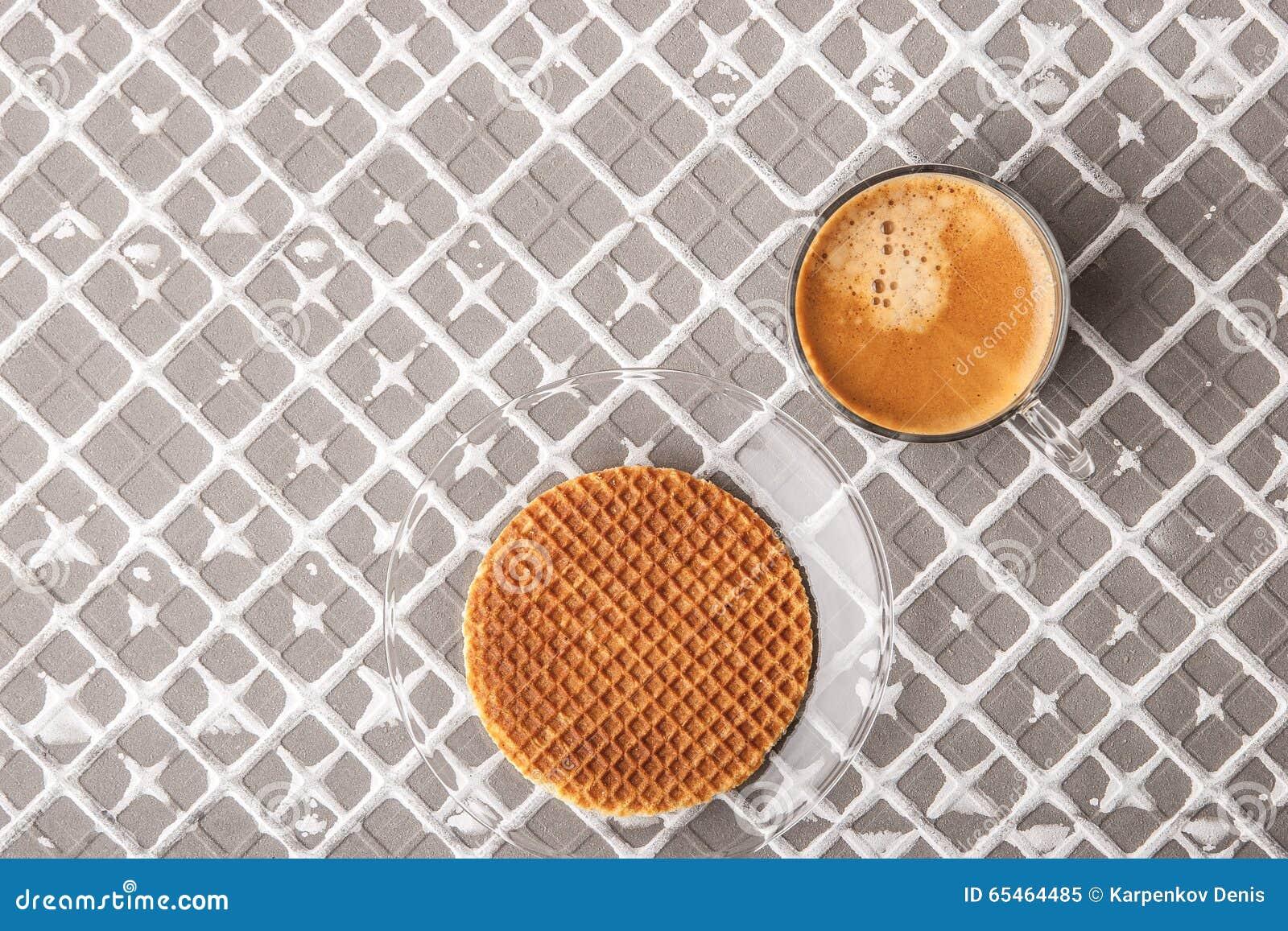 Kop van koffie met wafeltje op de hulpachtergrond