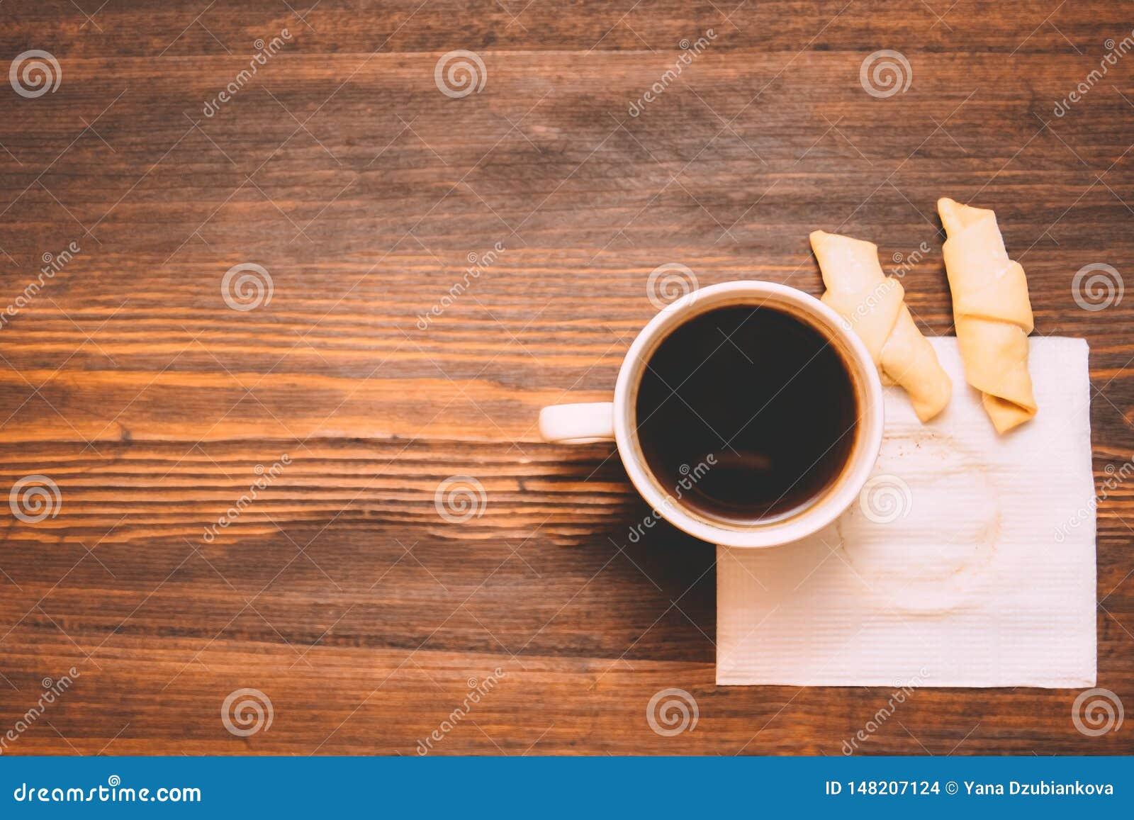 Kop van koffie op een wit servet met koekjes op een houten achtergrond