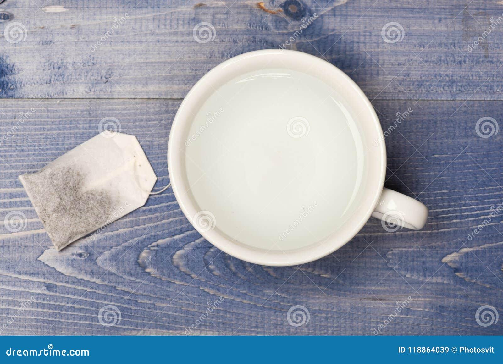 Kop of witte mok met transparante warm water en zak thee Het concept van de theetijd Mok met kokend water en theezakje wordt gevu