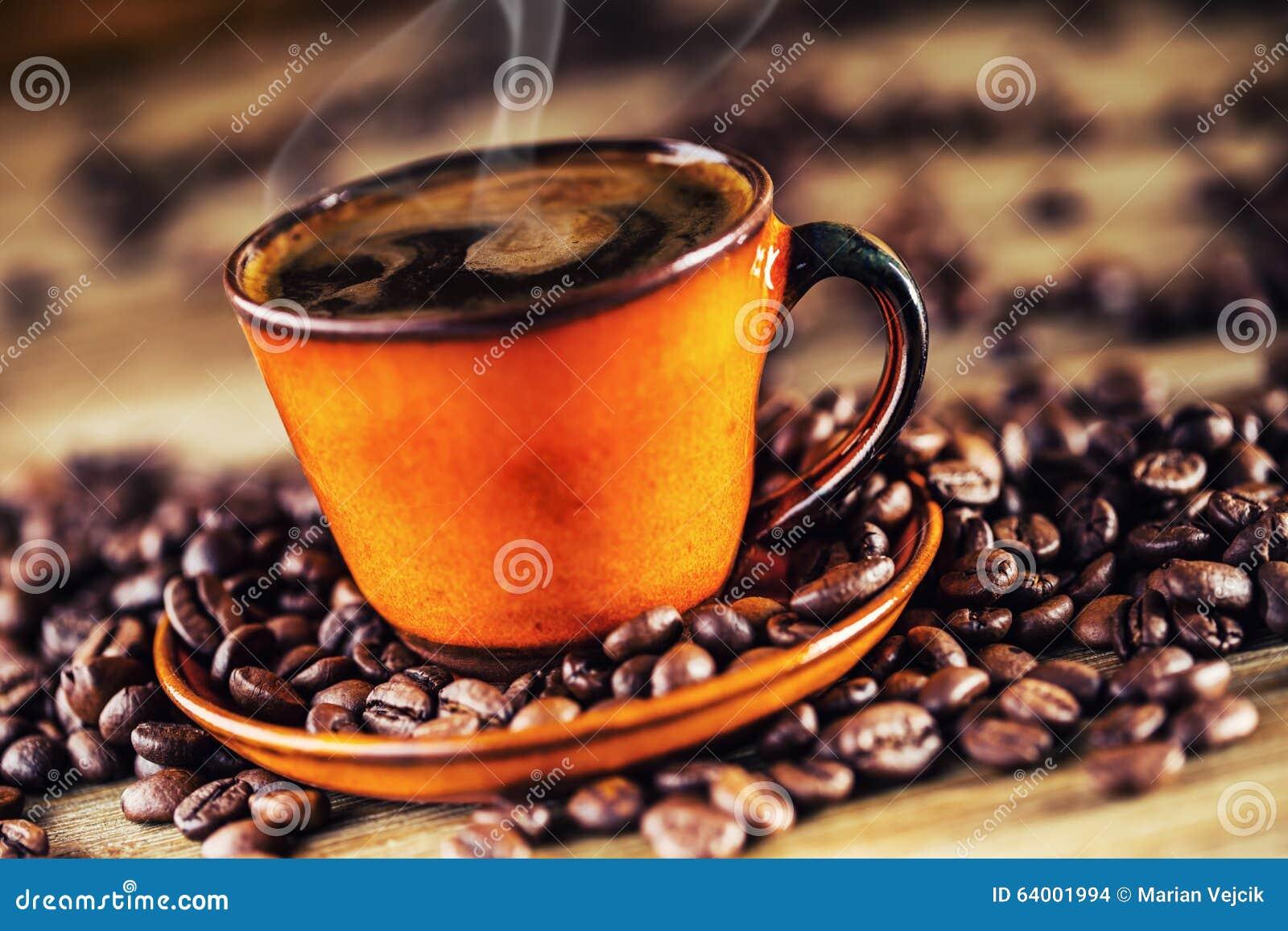 Kop zwarte koffie en gemorste koffiebonen Zoete croissant en een kop van koffie op de achtergrond