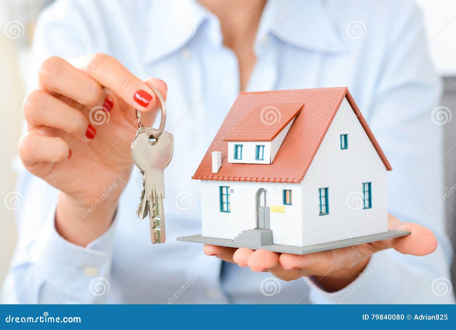 Kopend een huisconcept die met vrouwenhanden een model houden huisvest en sleutels