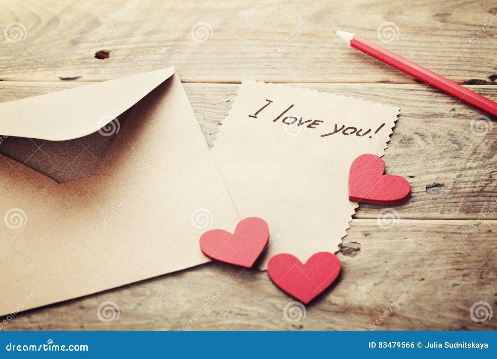 Koperta, list, czerwoni serca lub notatki, kocham ciebie na rocznika drewnianym stole dla walentynka dnia w retro tonowaniu