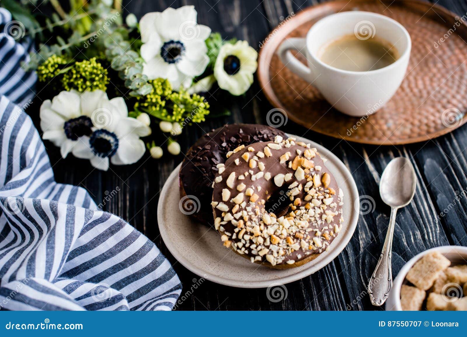 Kopp av donuts för coffe och för en choklad på svart trä