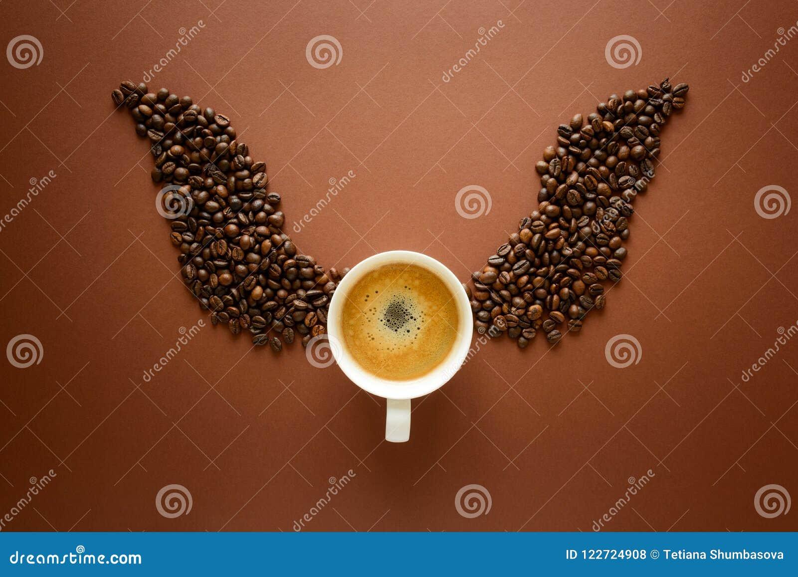 Kopp av espresso med vingar från kaffebönor på brun bakgrund Begrepp för bra morgon Top beskådar Lekmanna- lägenhet