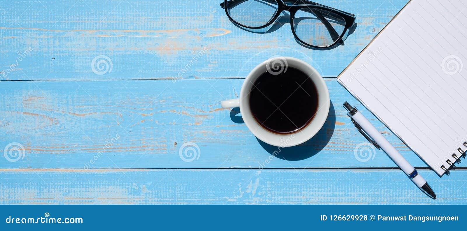 Kopp av svart kaffe med kontorstillförsel; penn-, anteckningsbok- och ögonexponeringsglas på blå trätabellbakgrund