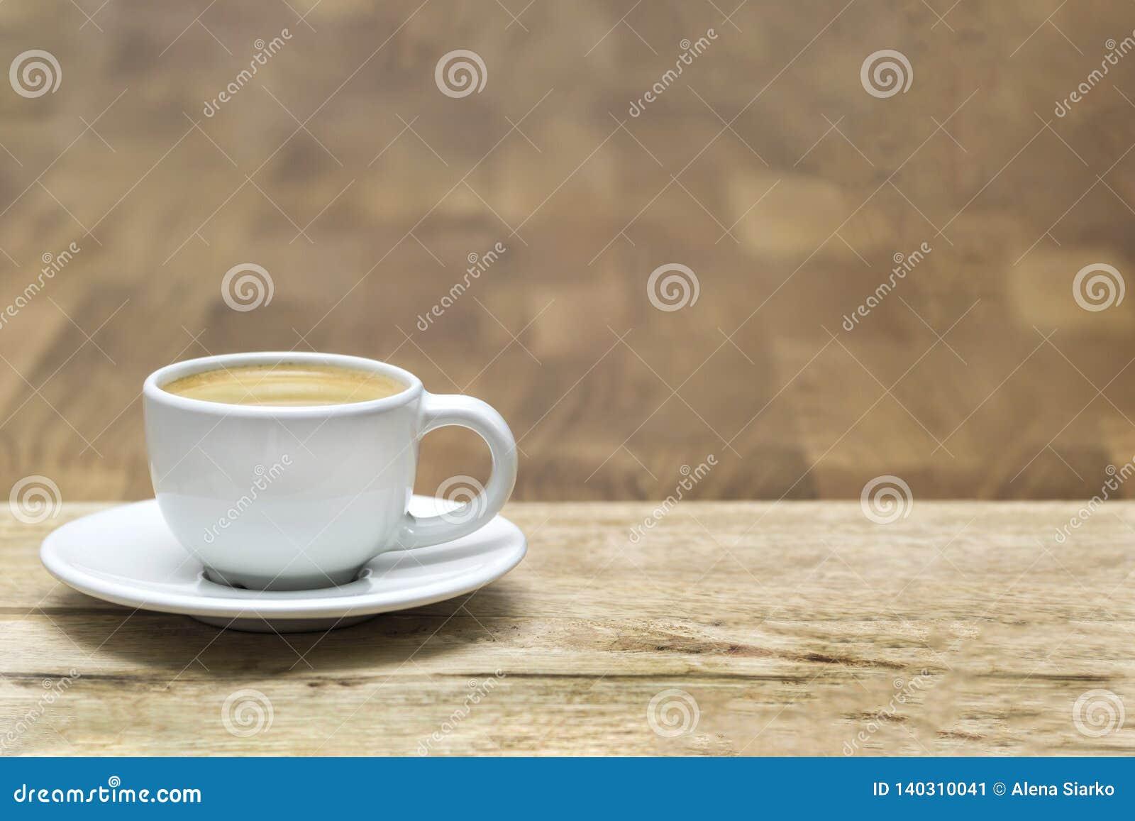 Kopp för vitt kaffe på en trätabell