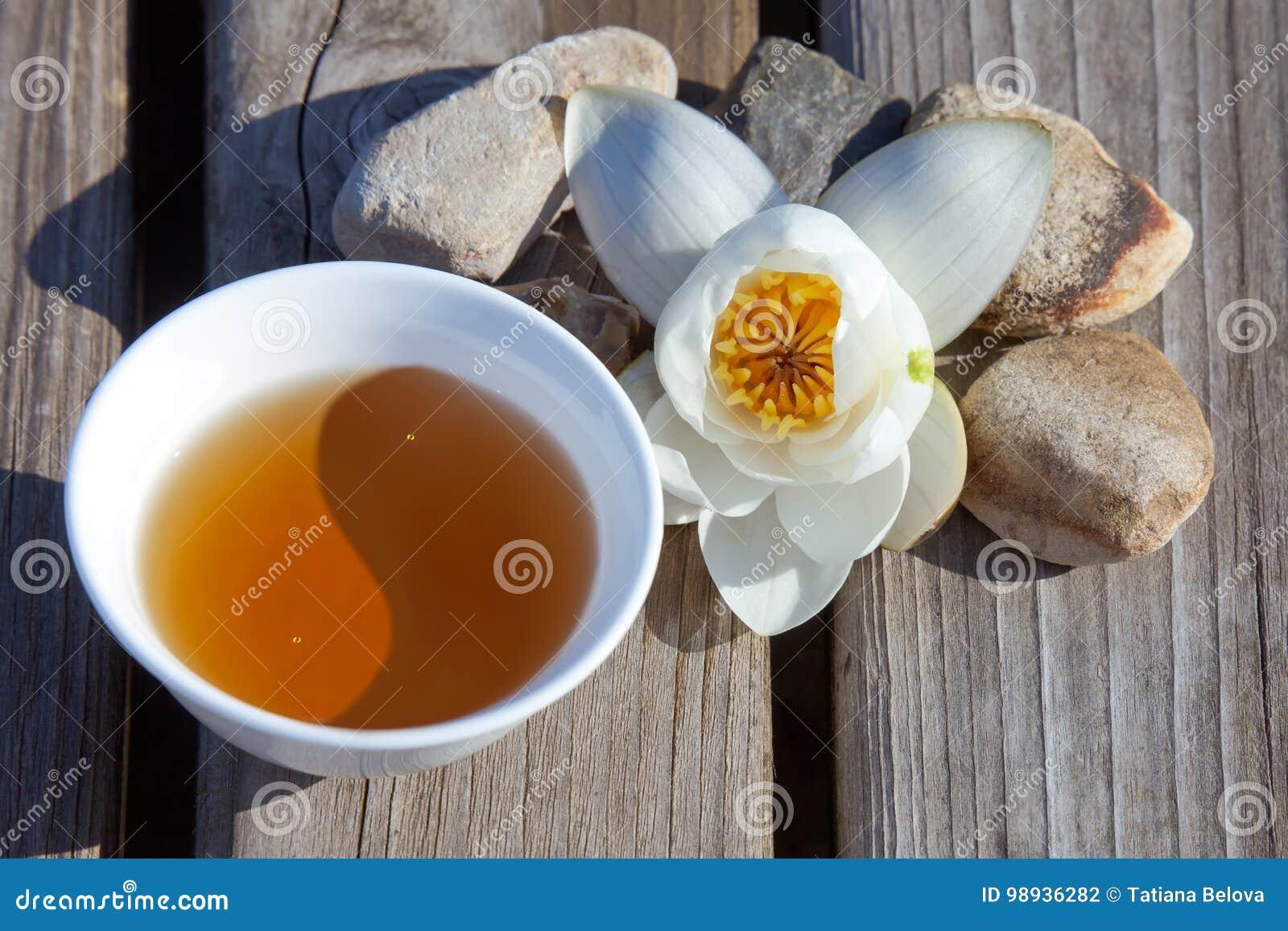 Kopp te i form av det Yin Yang symbolet med en näckros överkant
