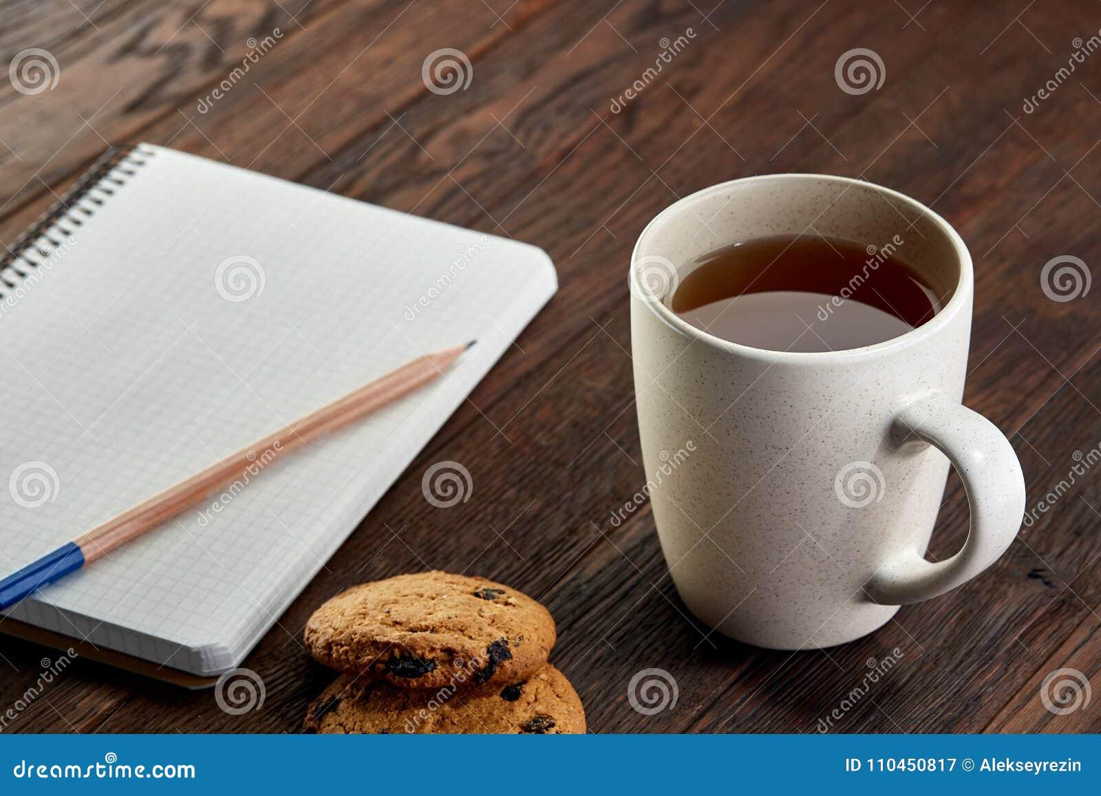 Kopp te med kakor, arbetsboken och en blyertspenna på en träbakgrund, bästa sikt