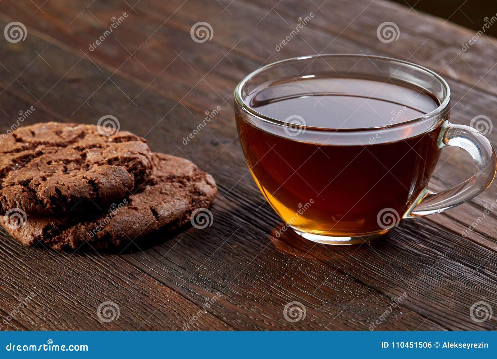 Kopp te med kakor på en skärbräda på en träbakgrund, bästa sikt