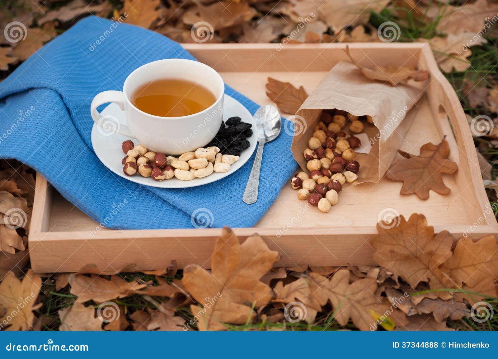 Kopp te och plattan med hasselnötter är på en servett
