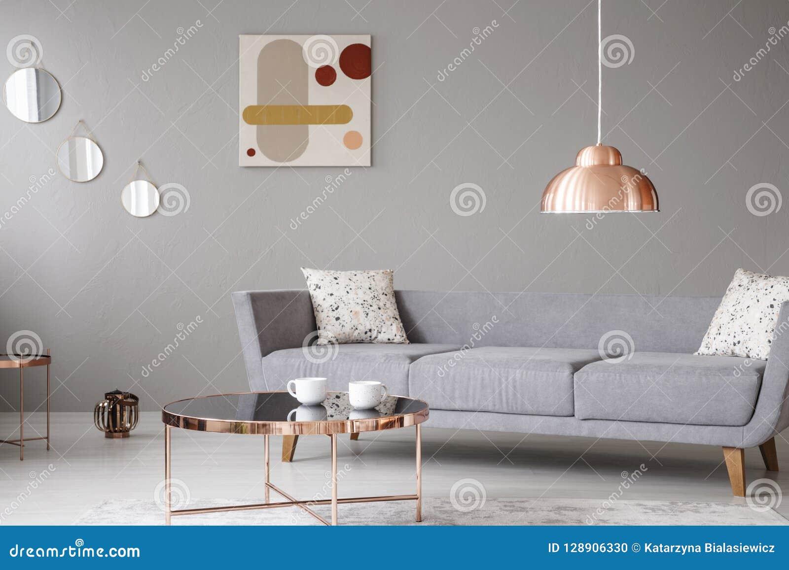 Kopparlamp- och kaffetabell framme av en modern soffa i en grå vardagsruminre