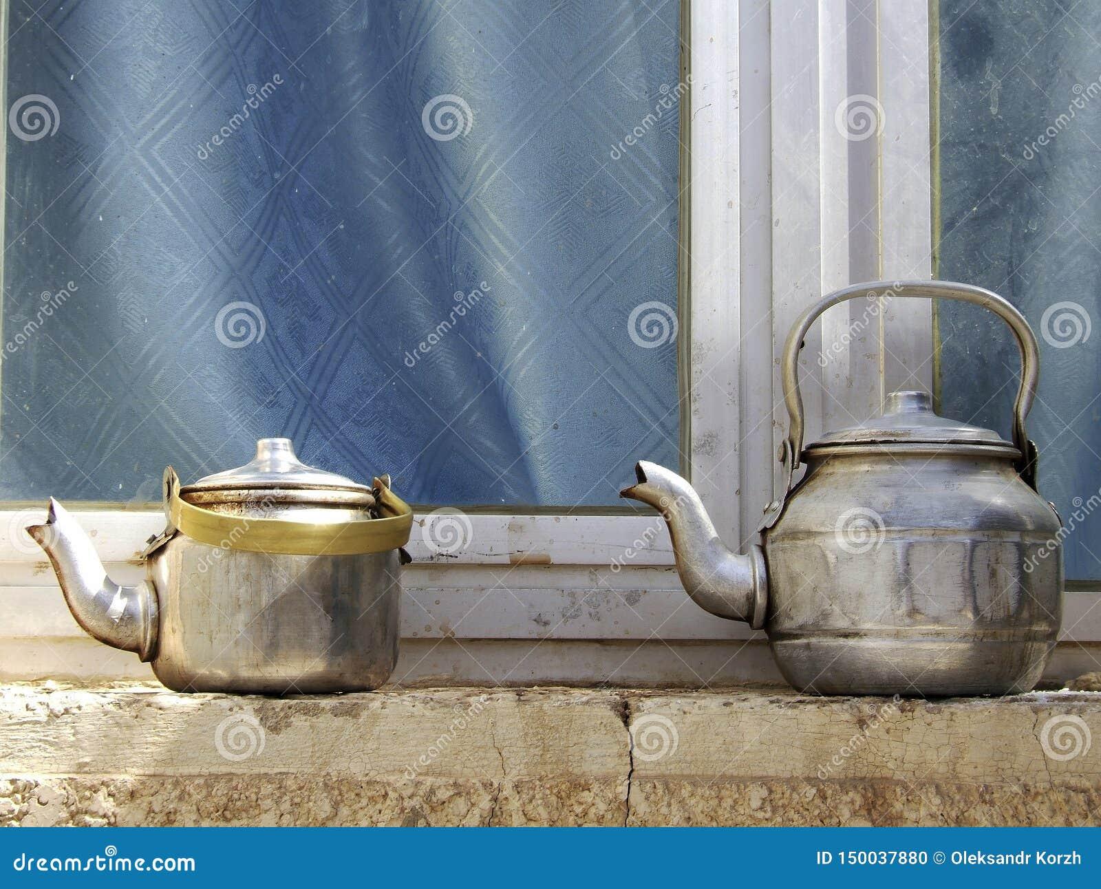 Koppartekannor som står till den konkreta fönsterbrädan, kokkärl på gatan, shoppar fönstret för exponeringsglas
