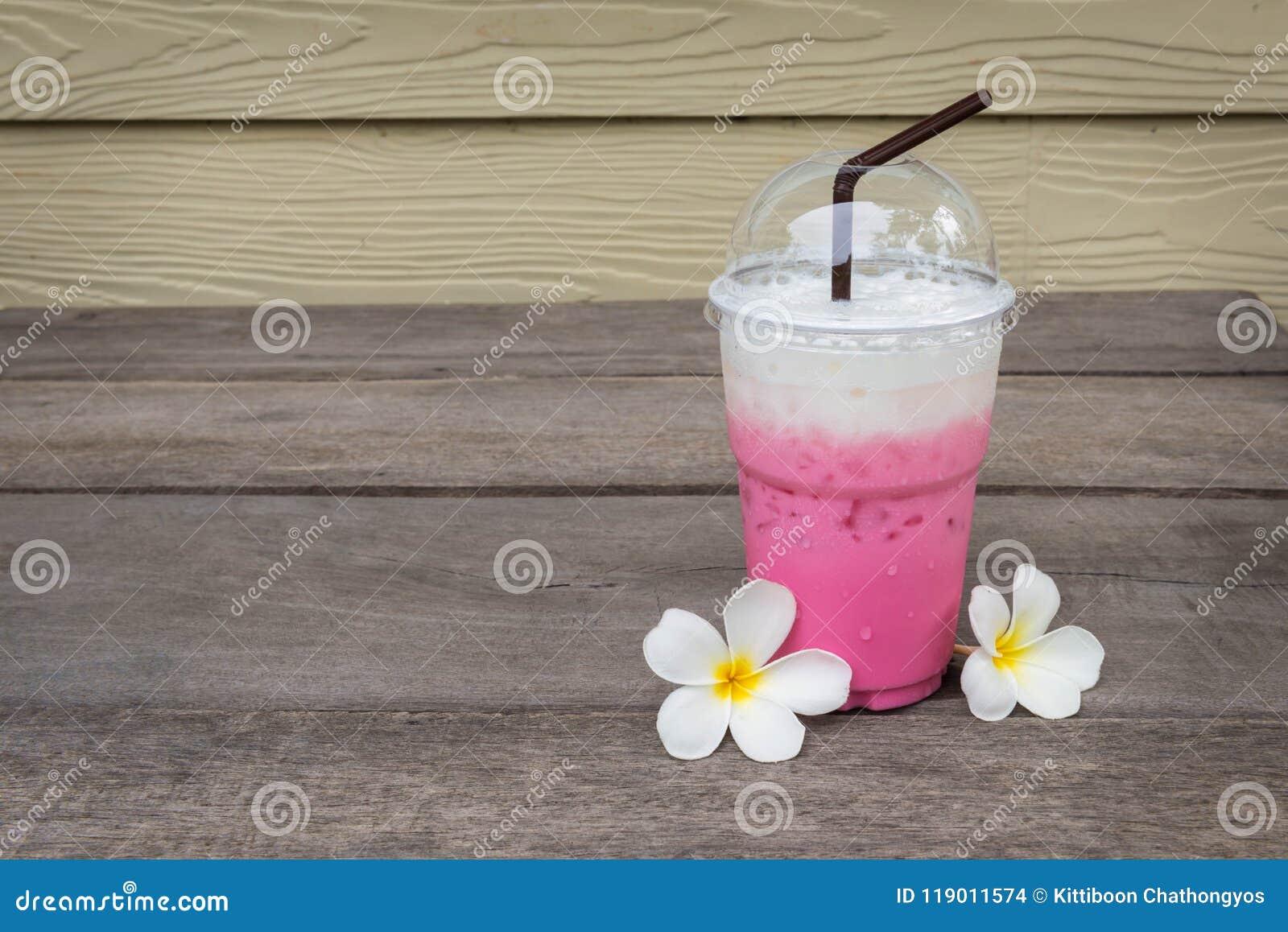 Koppen av rosa is mjölkar nära Plumeriablommor på trägolv