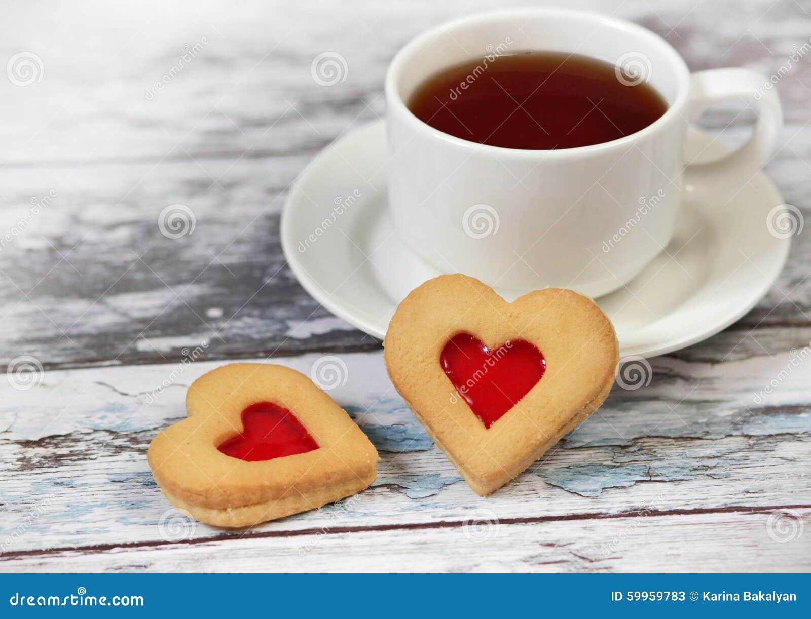 Koppen av svart te och hjärta formade kakor