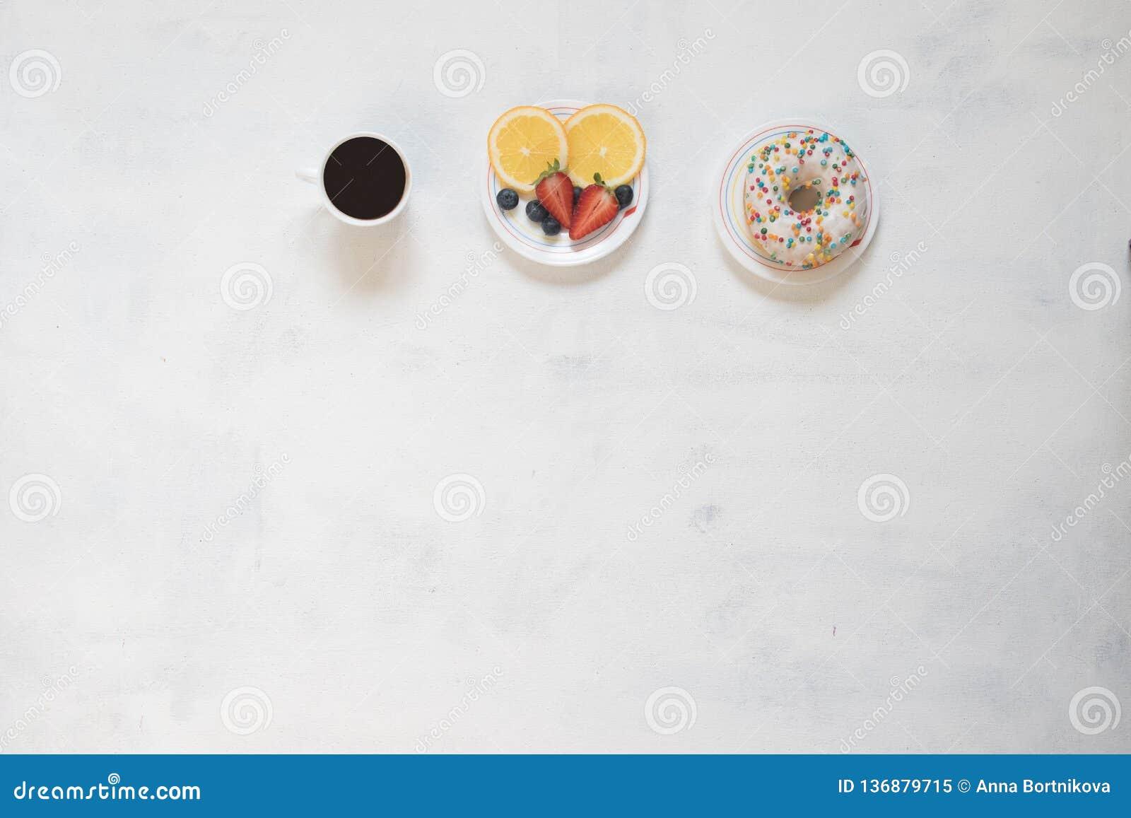 Koppen kaffe och munken med ostmassakräm dekorerade med smulor av röd frukt på vit bakgrund