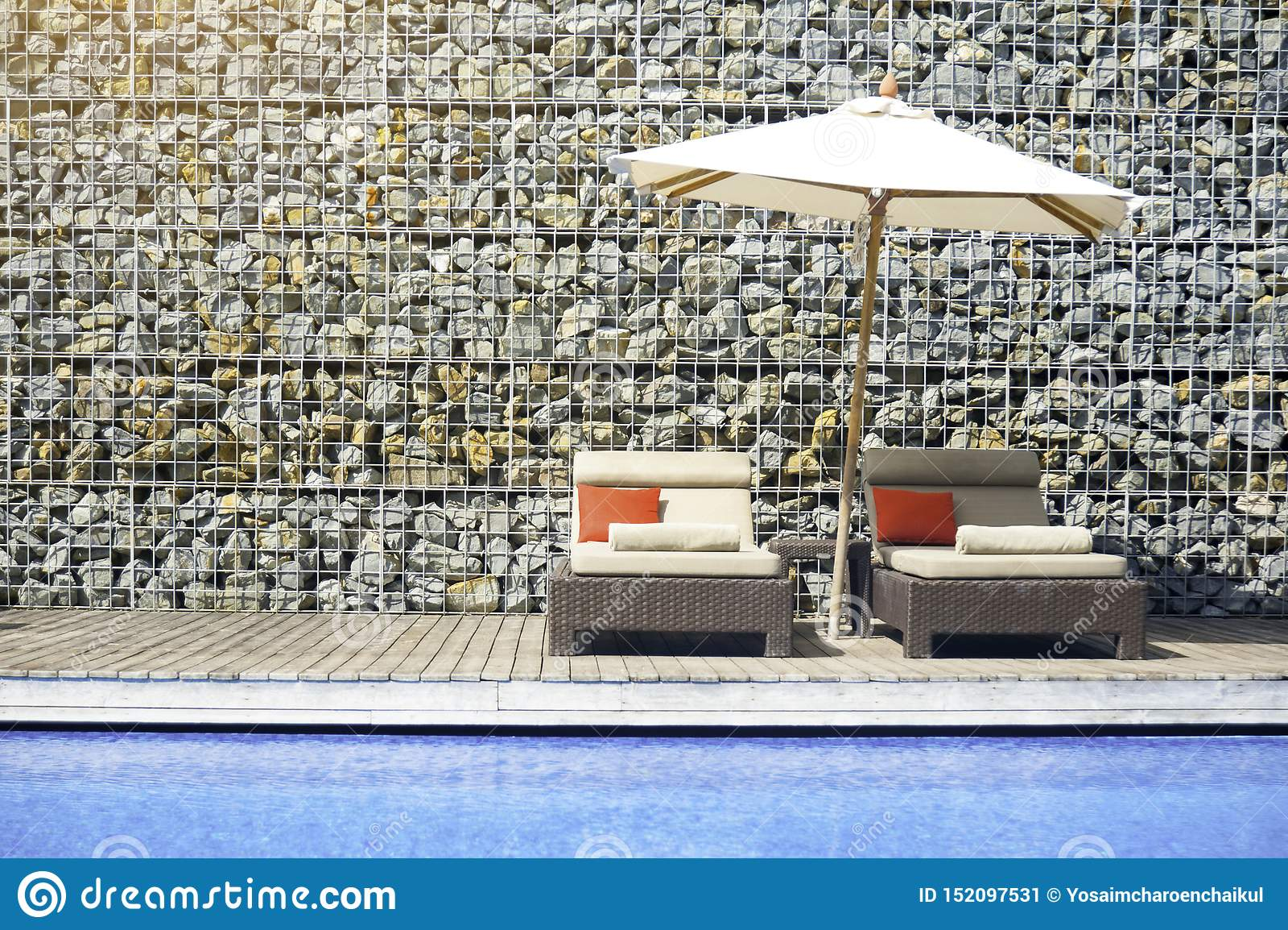 Koppla av atmosfär av simbassänghotellen med stenväggar som dekoreras i sommaren Stol som ska kopplas av vid hotellpöldäcket in