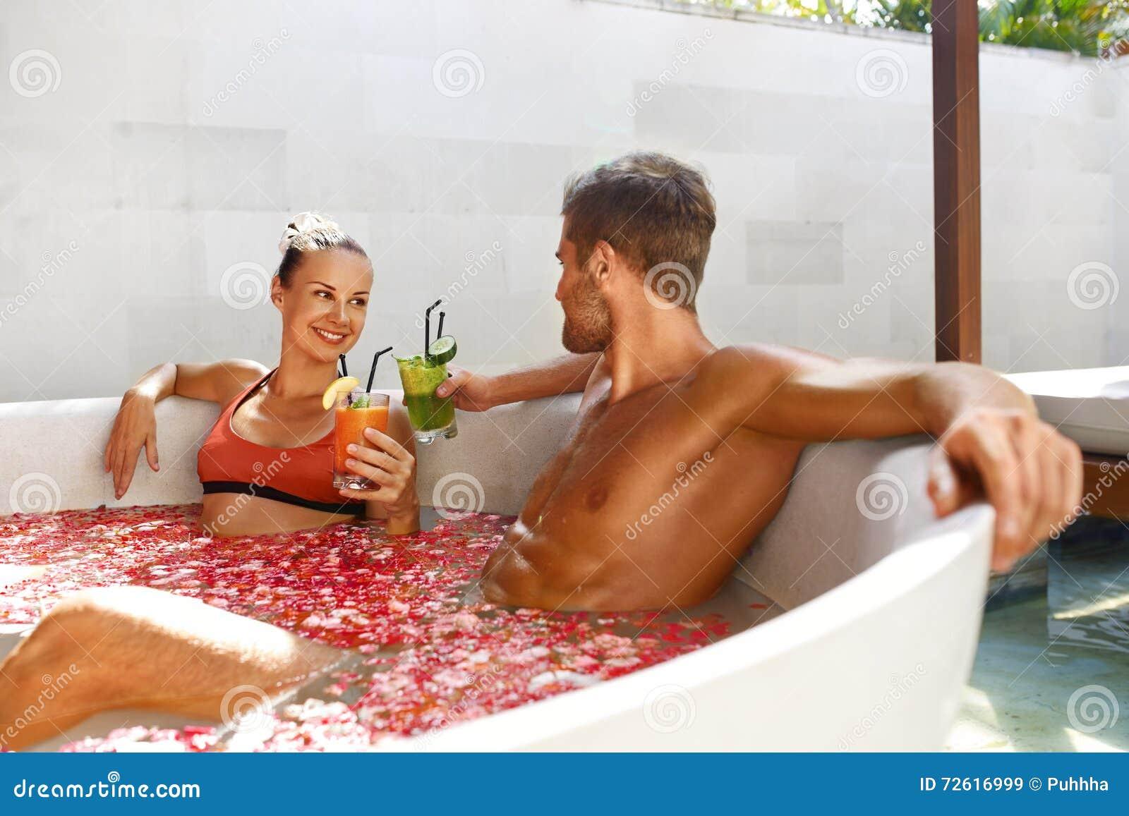 Koppla av brunnsorten Par som är förälskade i blommabadet som dricker drinkar