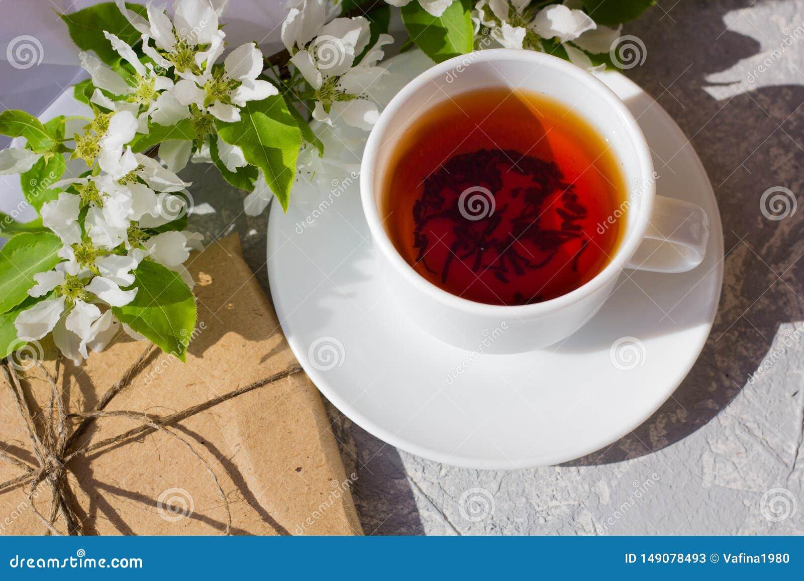 Koppla av tid och lycka med kopp te med bland den nya vårblomman