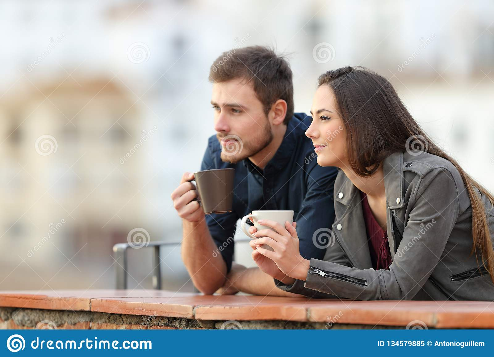 Koppla ihop att koppla av dricka kaffe i en balkong på semester