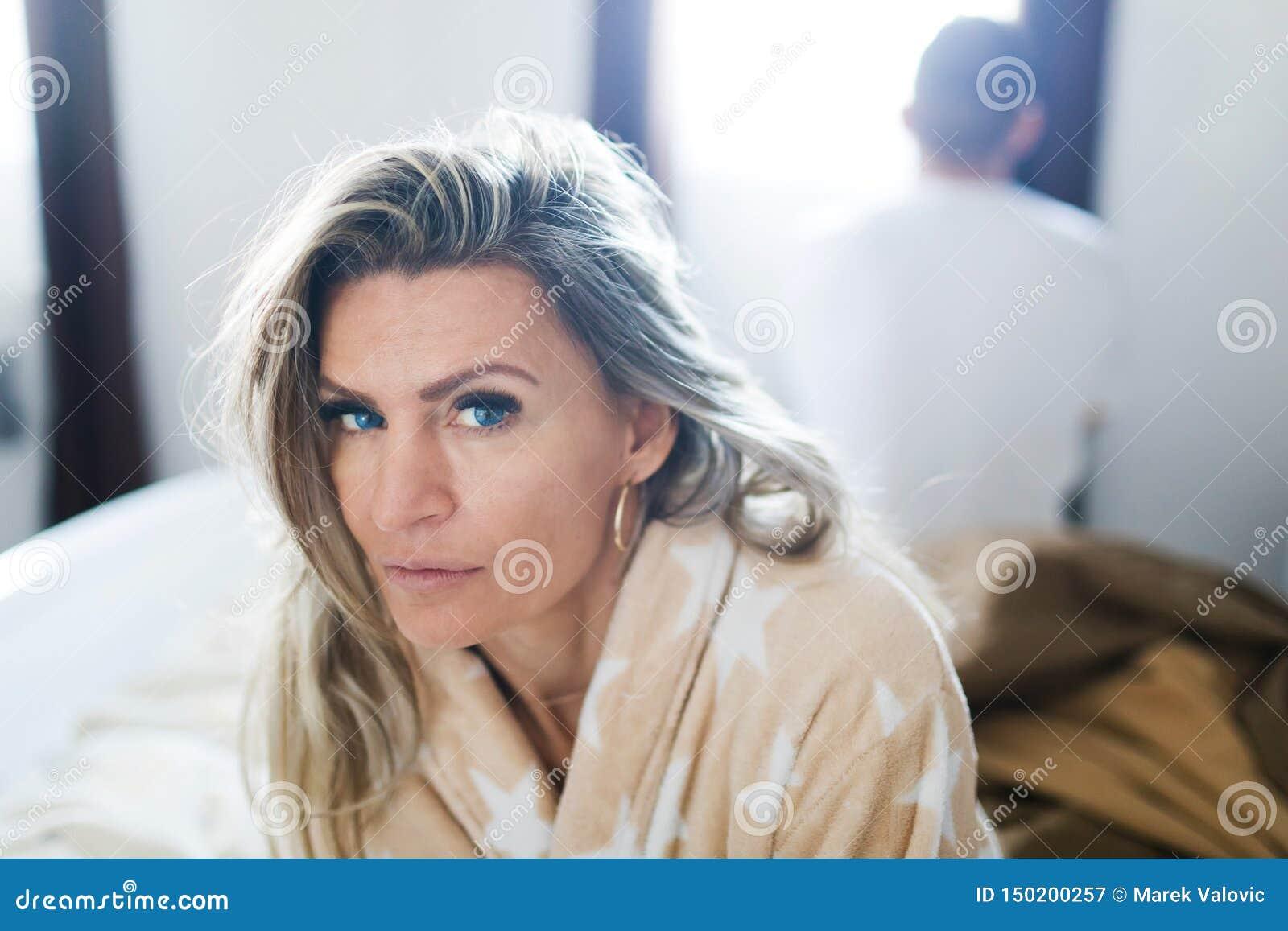 Koppla ihop att ha kris i s?ng Kvinna som sitter på sängs kant - som är tillbaka för att dra tillbaka