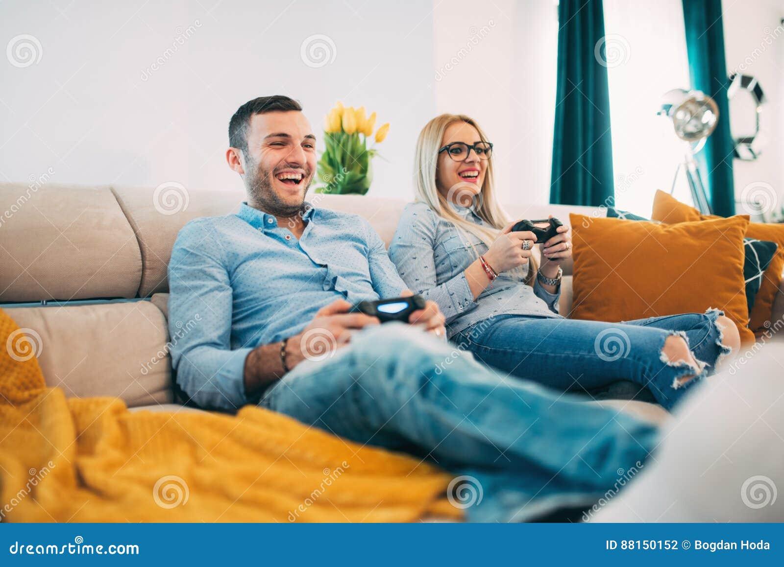 Koppla ihop att ha roligt och att skratta, medan spela videospel i modern vardagsrum