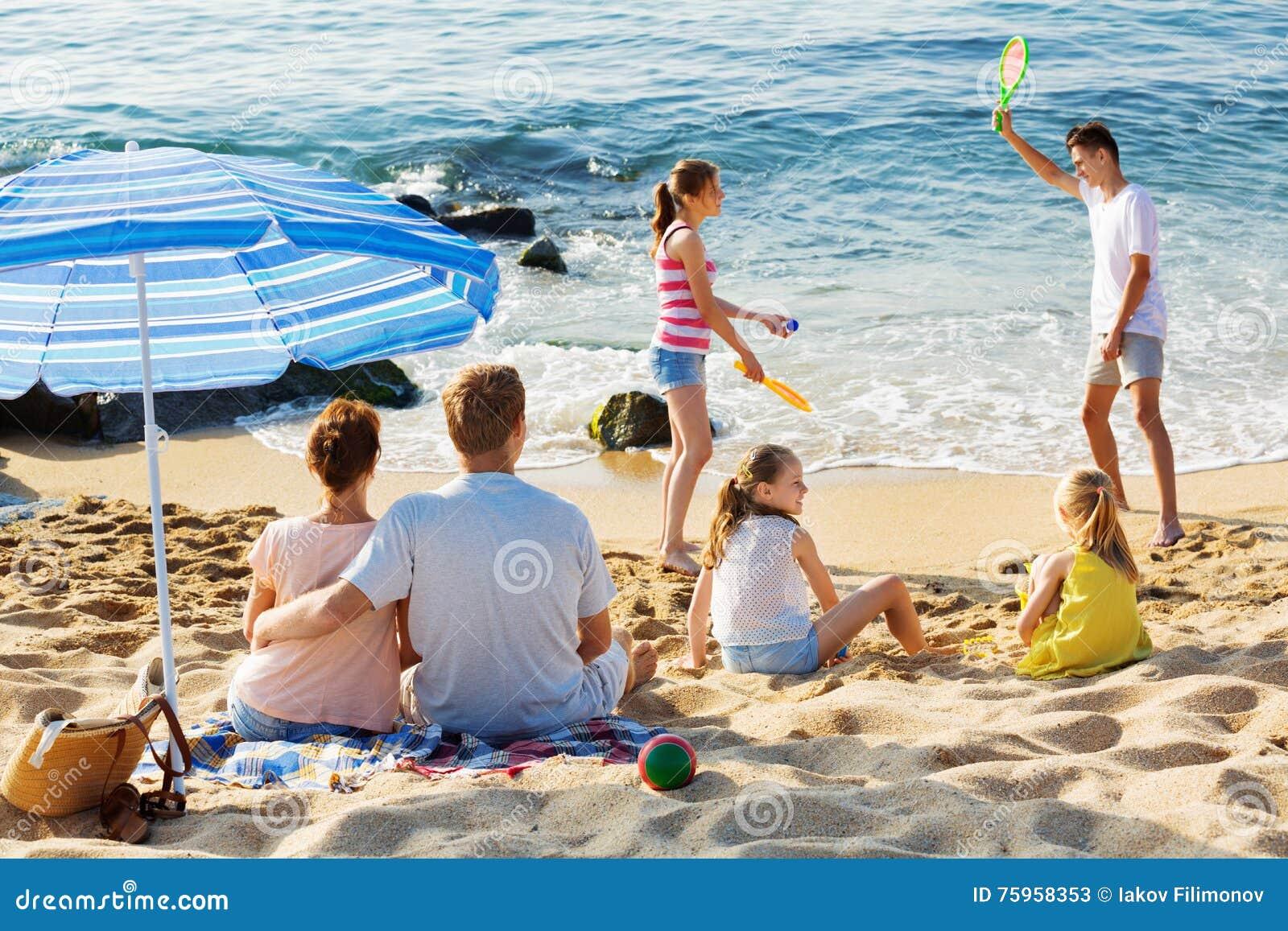 Koppla ihop att koppla av på stranden medan deras ungar som spelar aktiva lekar