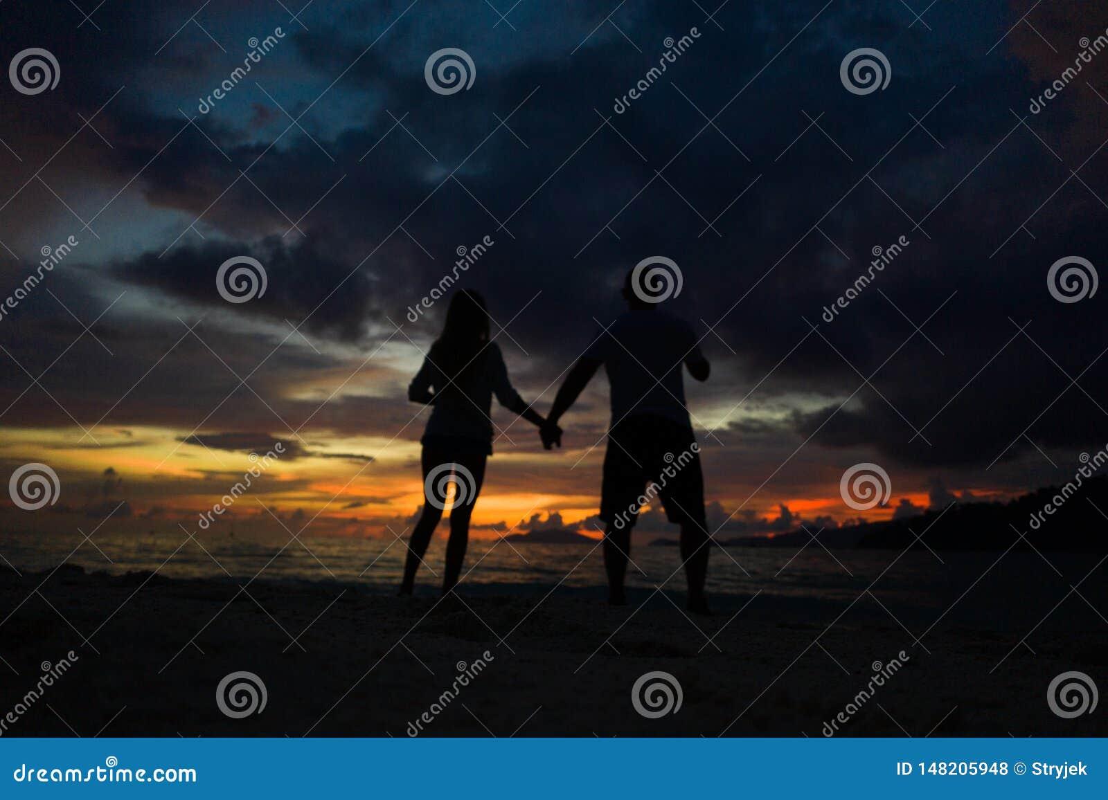 Koppla ihop att rymma händer på stranden med en härlig solnedgång i bakgrund