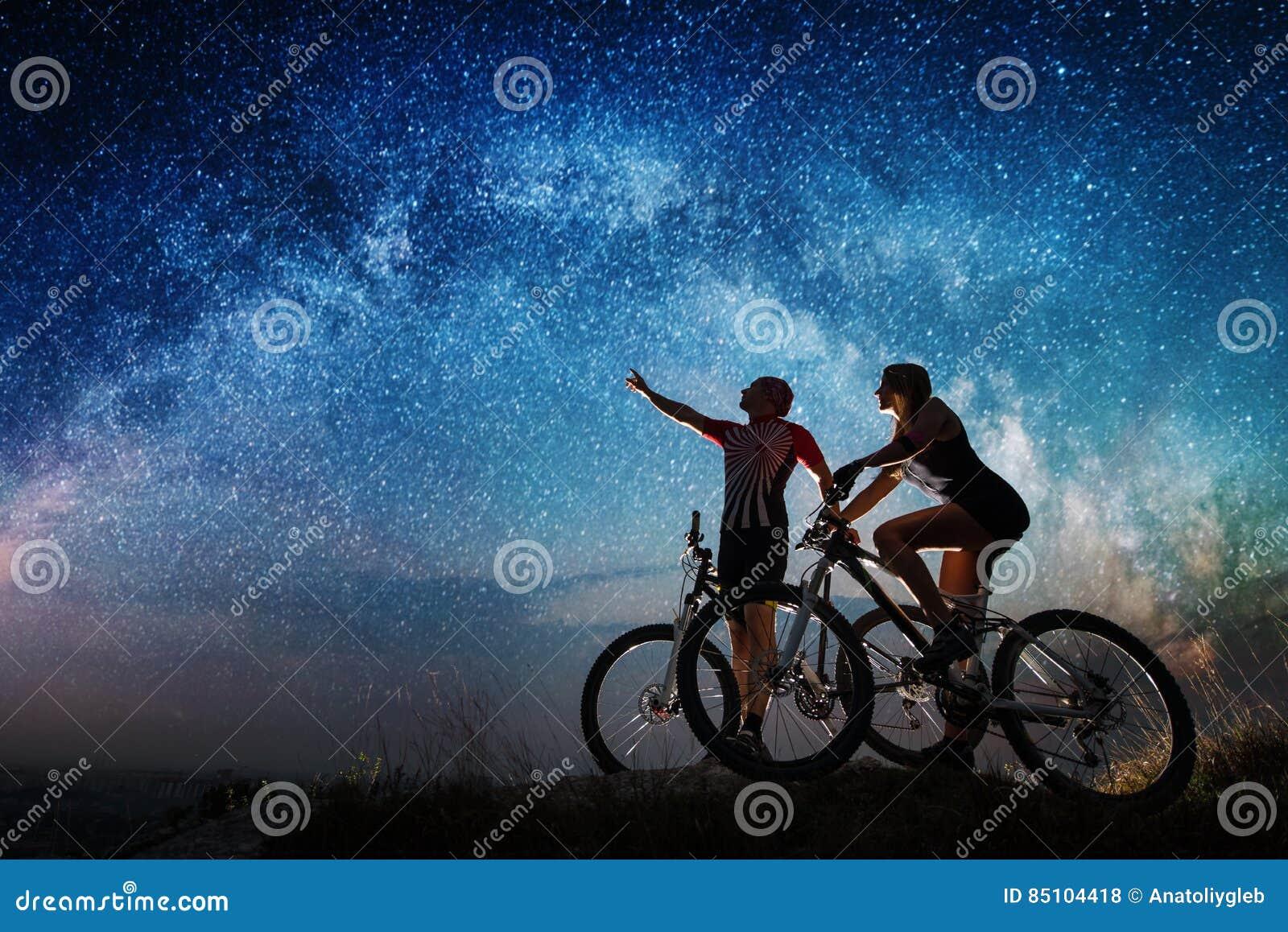 Koppla ihop cyklister med mountainbiken på natten under stjärnklar himmel