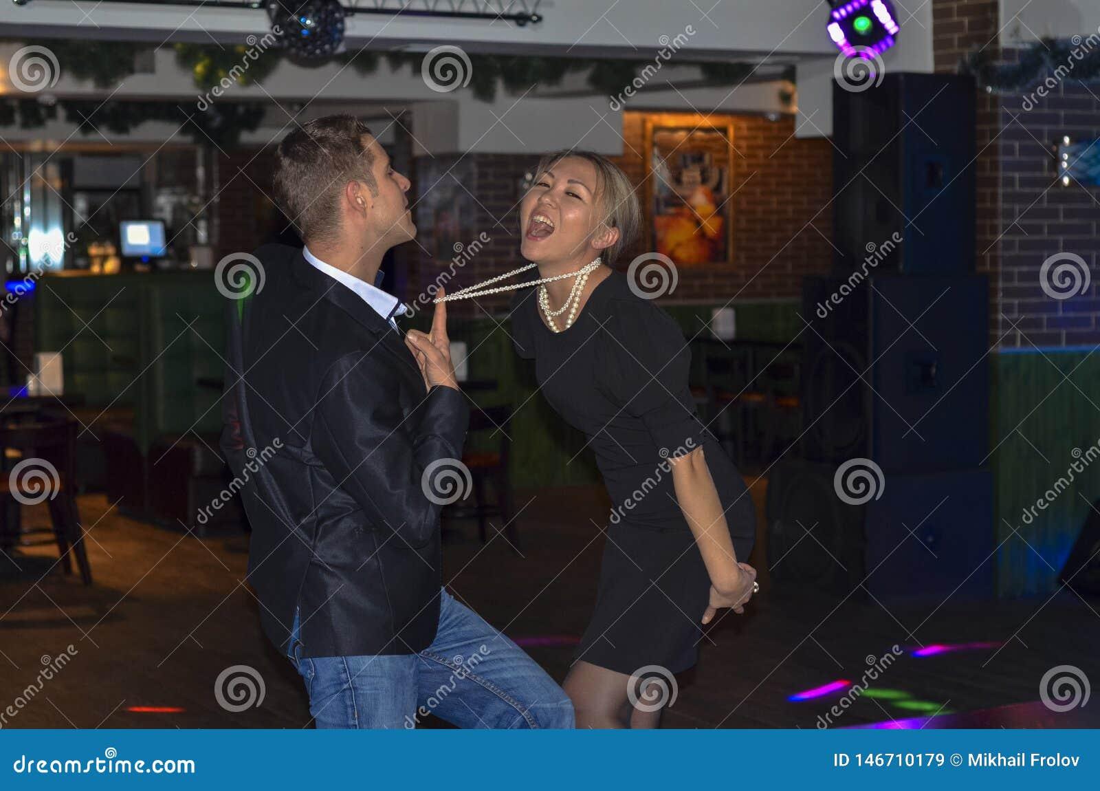 Koppla ihop dansen i en st?ng passionerad dans Deltagare i klubban Grabben drar flickan vid p?rlorna