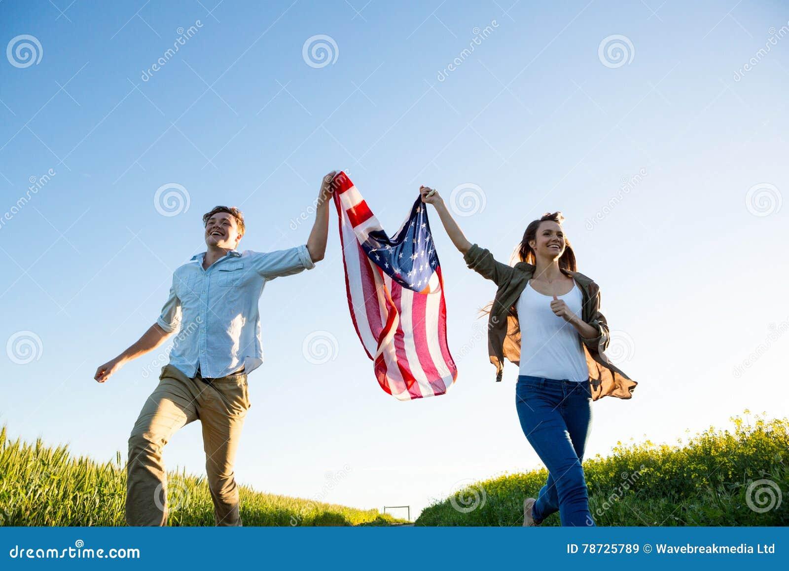 Koppla ihop den hållande amrican flaggan och spring i fält