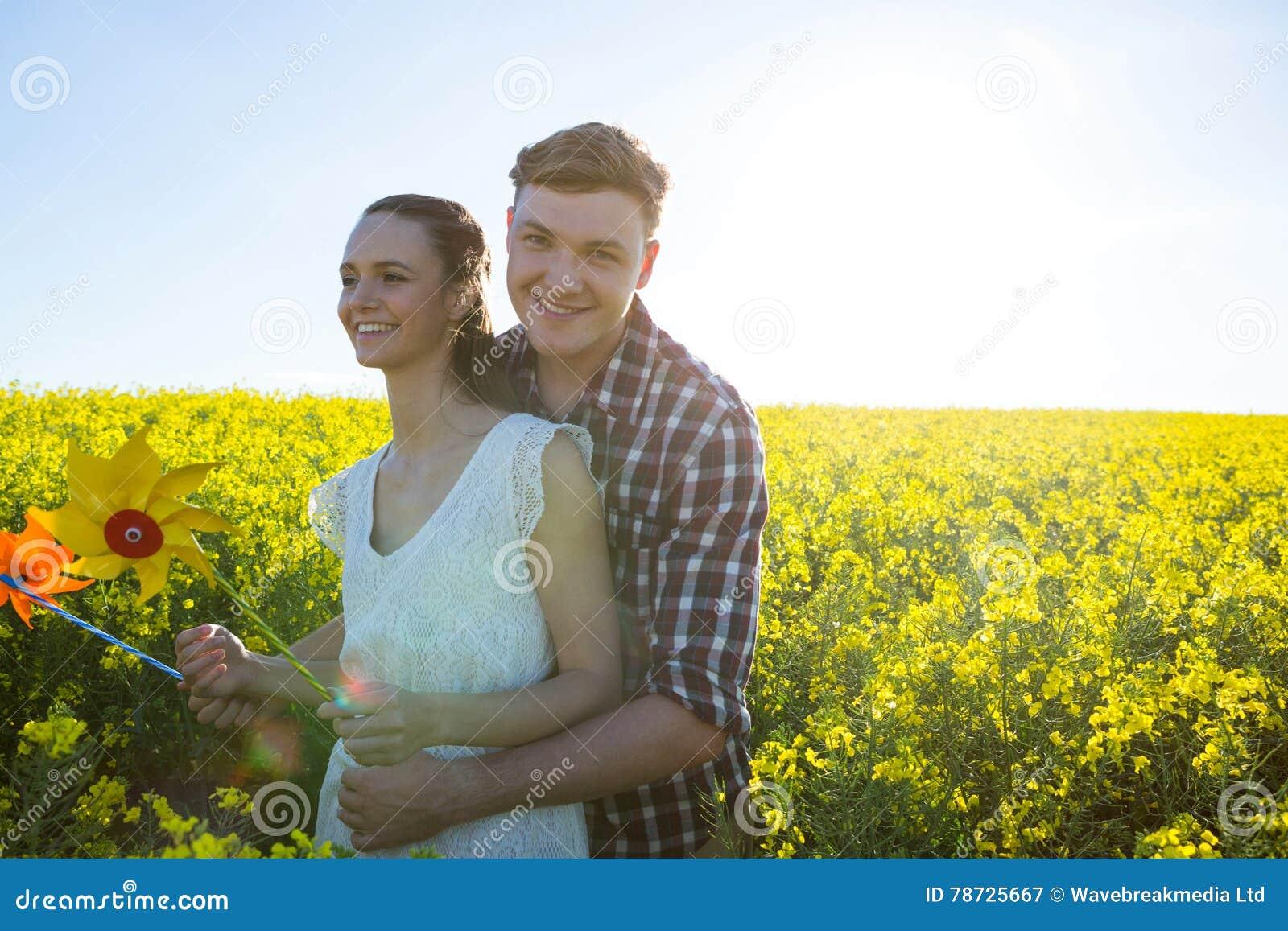 Koppla ihop den hållande lilla solen och att omfamna sig i senapsgult fält