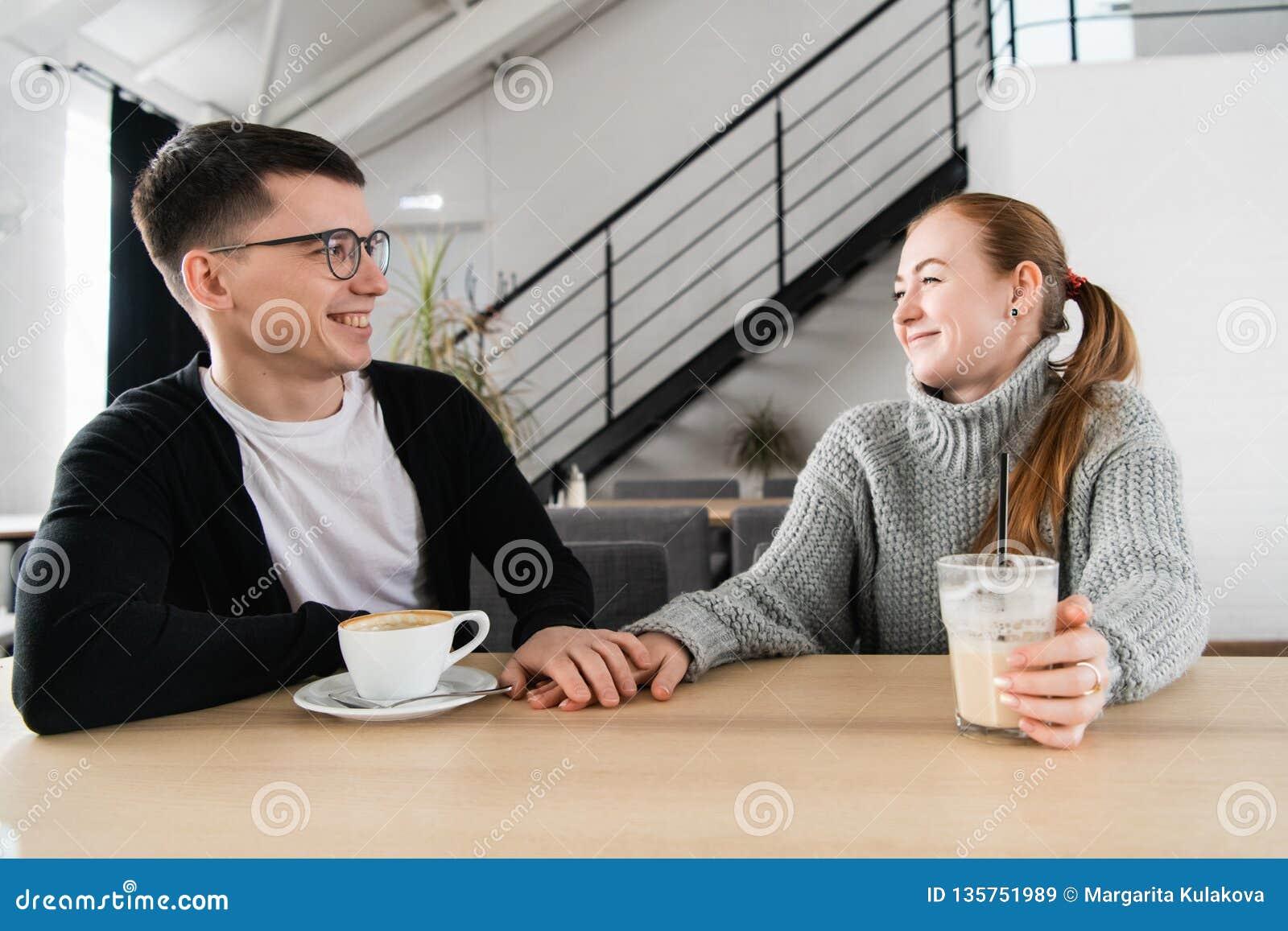 Koppla ihop förälskat sammanträde i kafét som ser de och rymmer händer