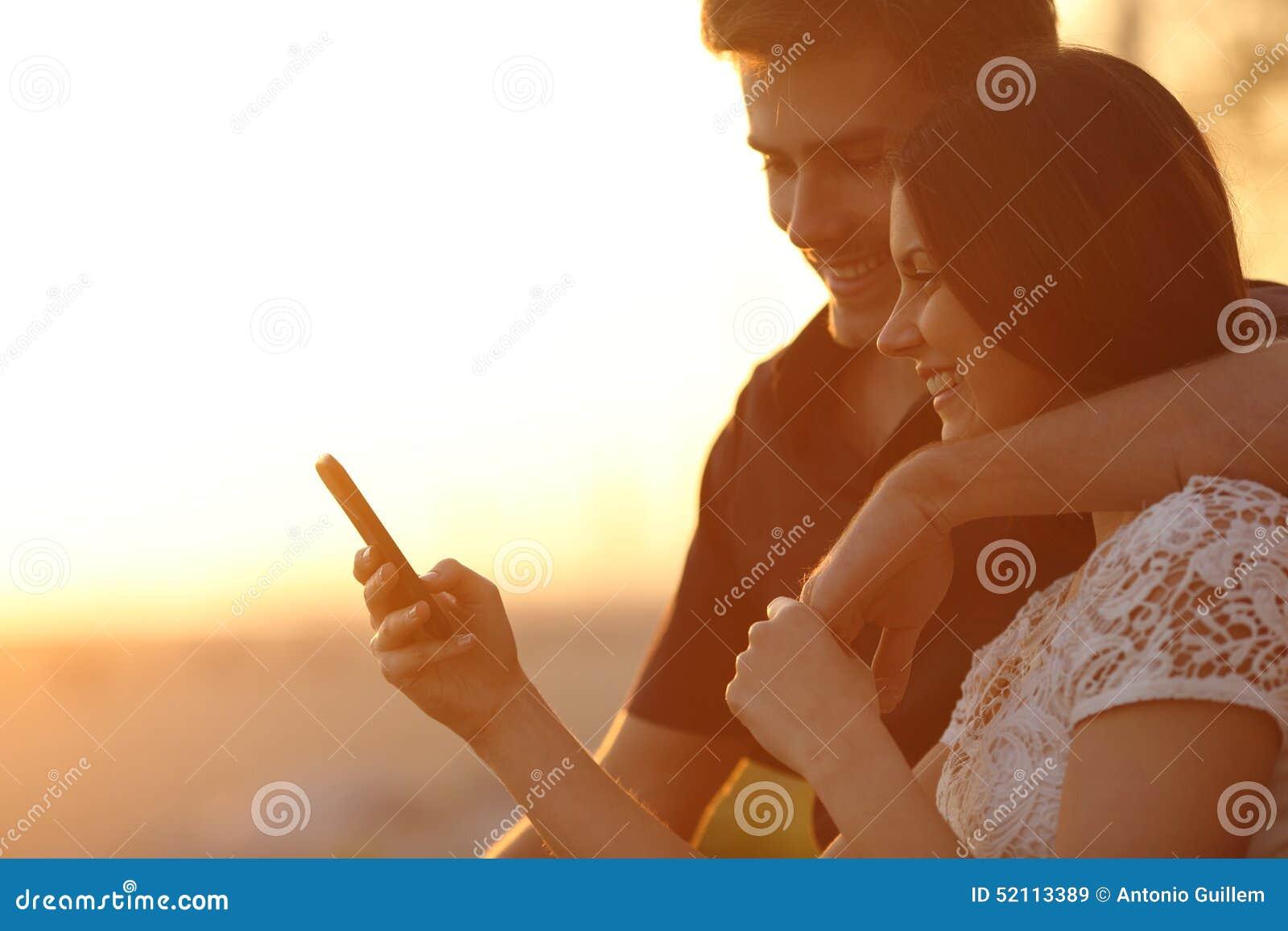 Koppla ihop genom att använda en smartphone i en solnedgång tillbaka tänder
