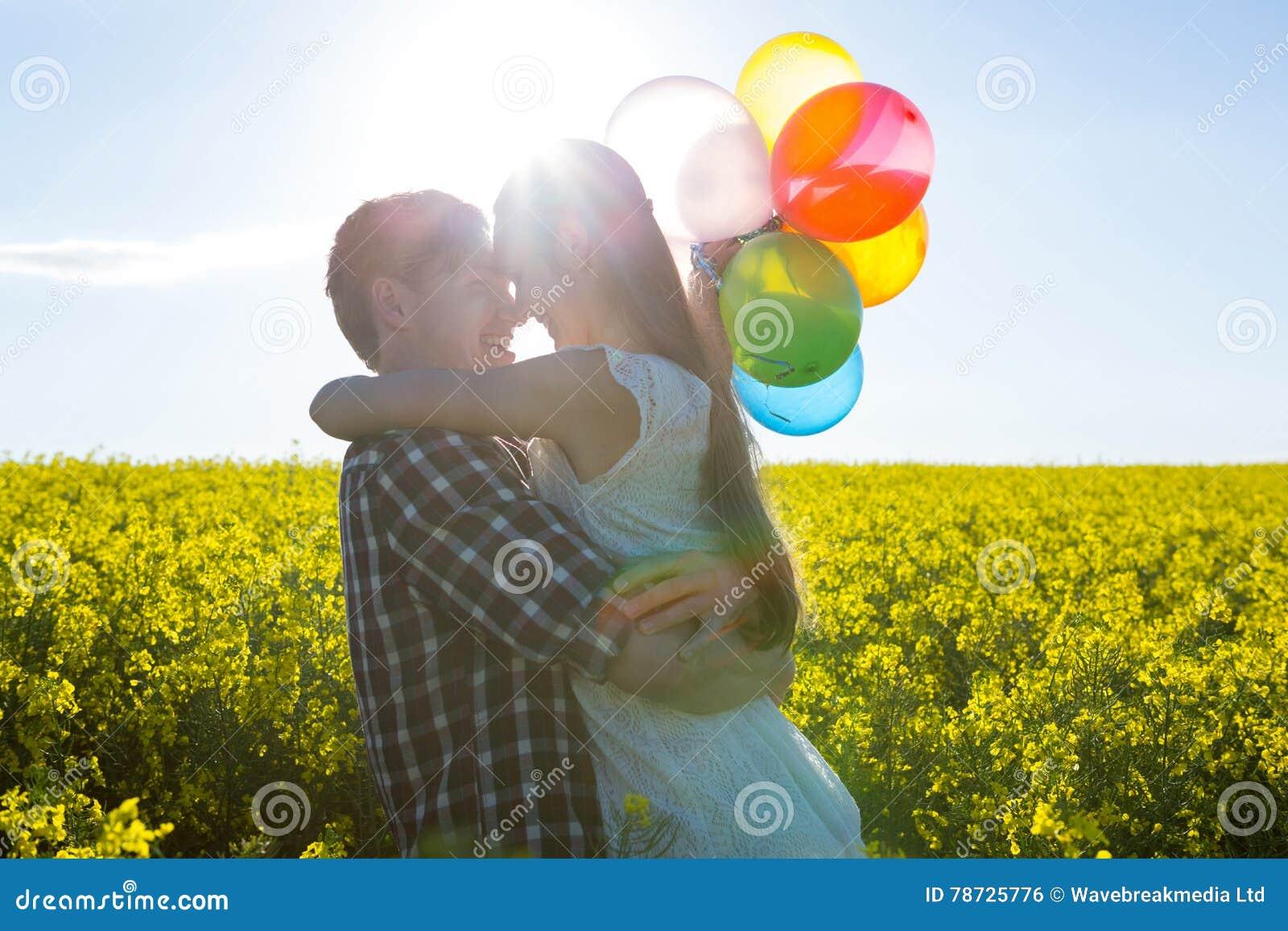 Koppla ihop hållande färgrika ballonger och att omfamna sig i senapsgult fält