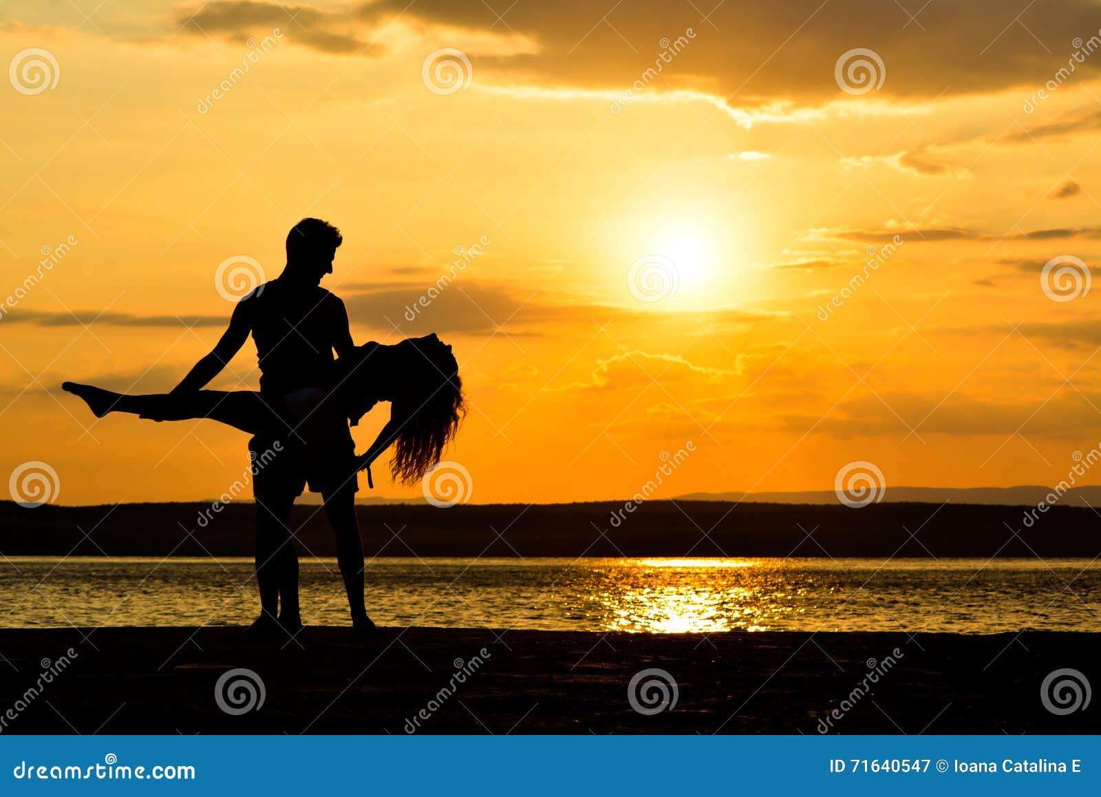 Koppla ihop konturer som rymmer på solnedgången av havet som dansar