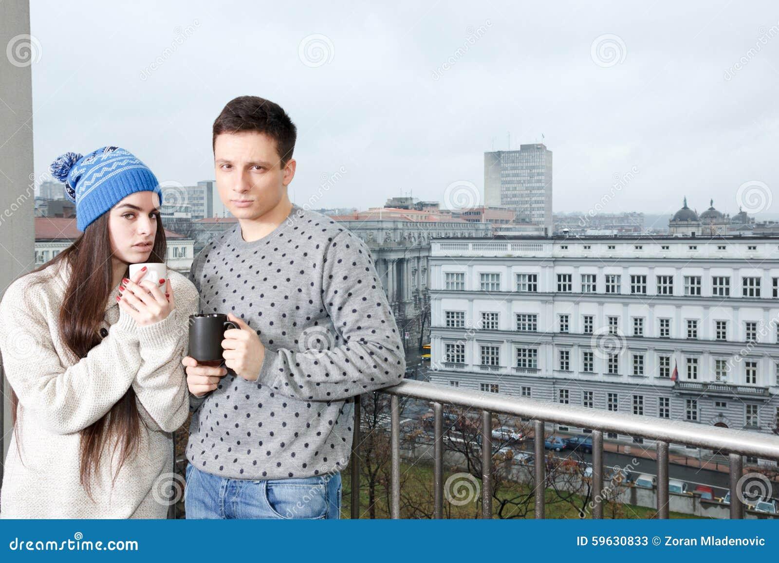 Koppla ihop lyckligt förälskat krama nära räcket med kopp te eller Co