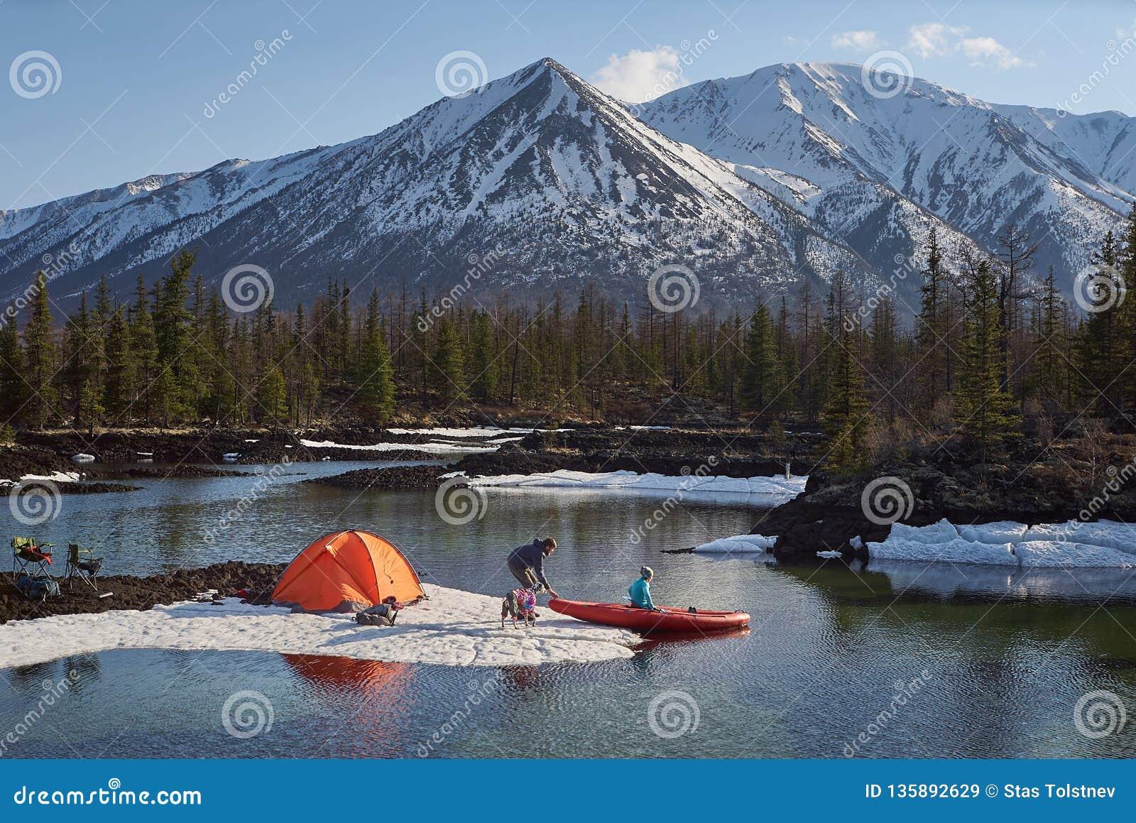 Koppla ihop mannen och kvinnan i ett läger på bergterräng Sjökust med kanoten