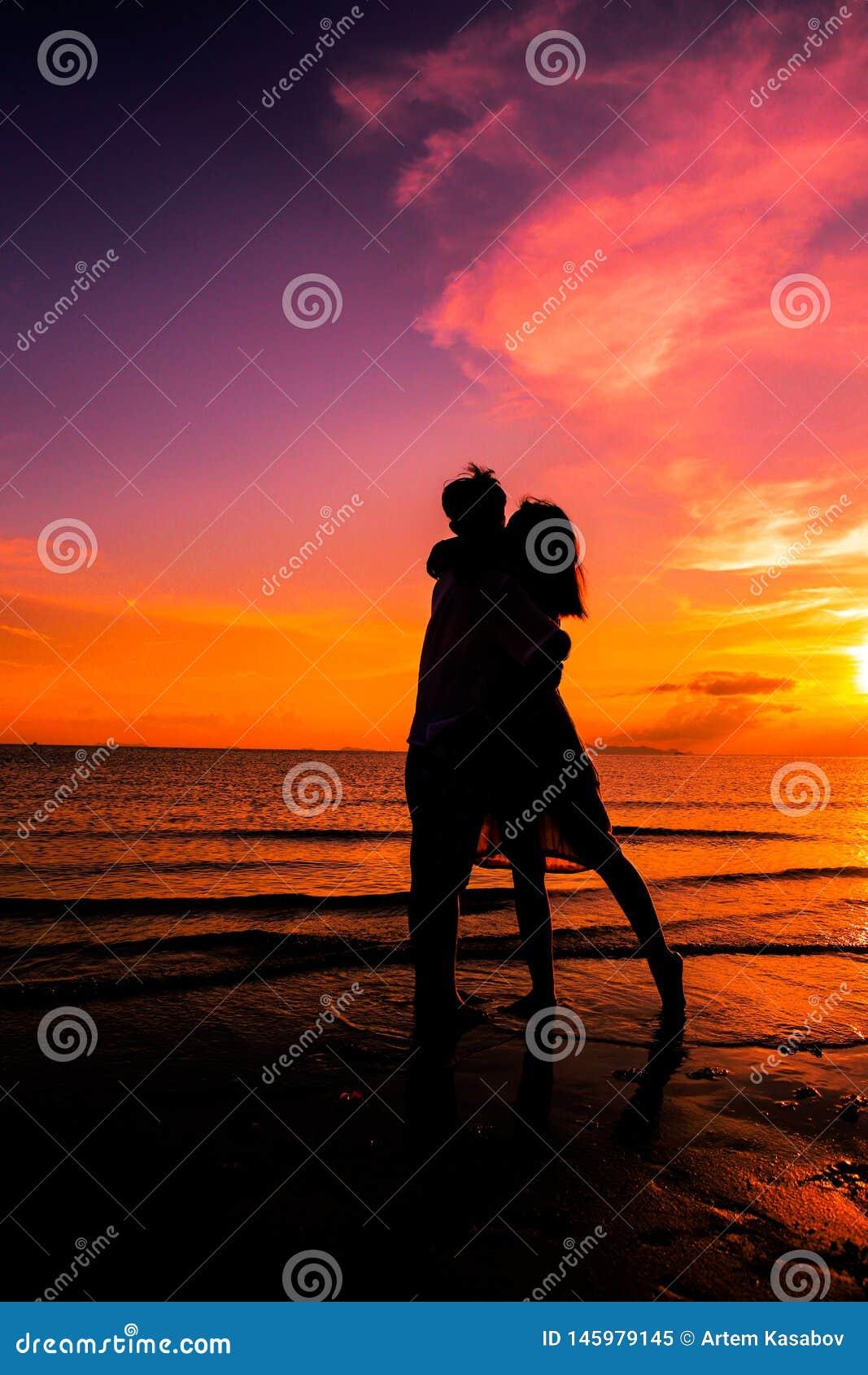 Koppla ihop p? stranden p? solnedg?ngkontur-romantiker sommar