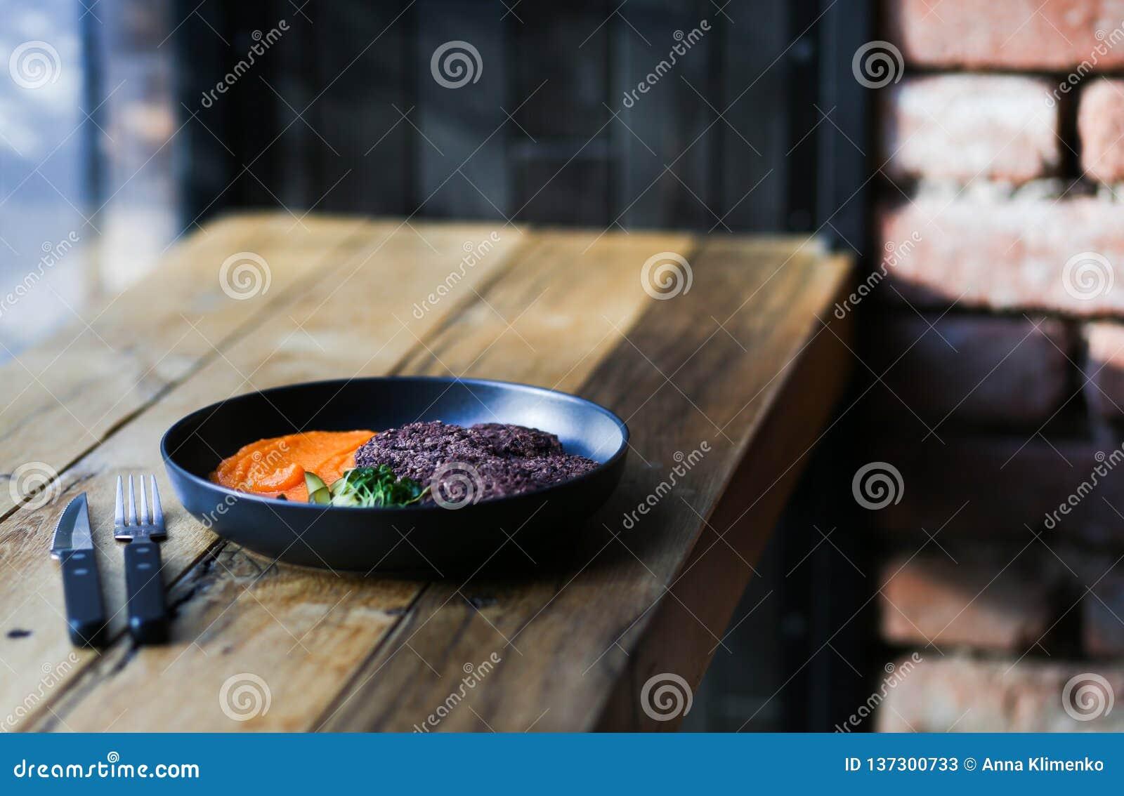 Kopplar ihop sunda svarta riskotletter för strikt vegetarian som tjänas som med orange morötter, och microgreeens och decafkaffe