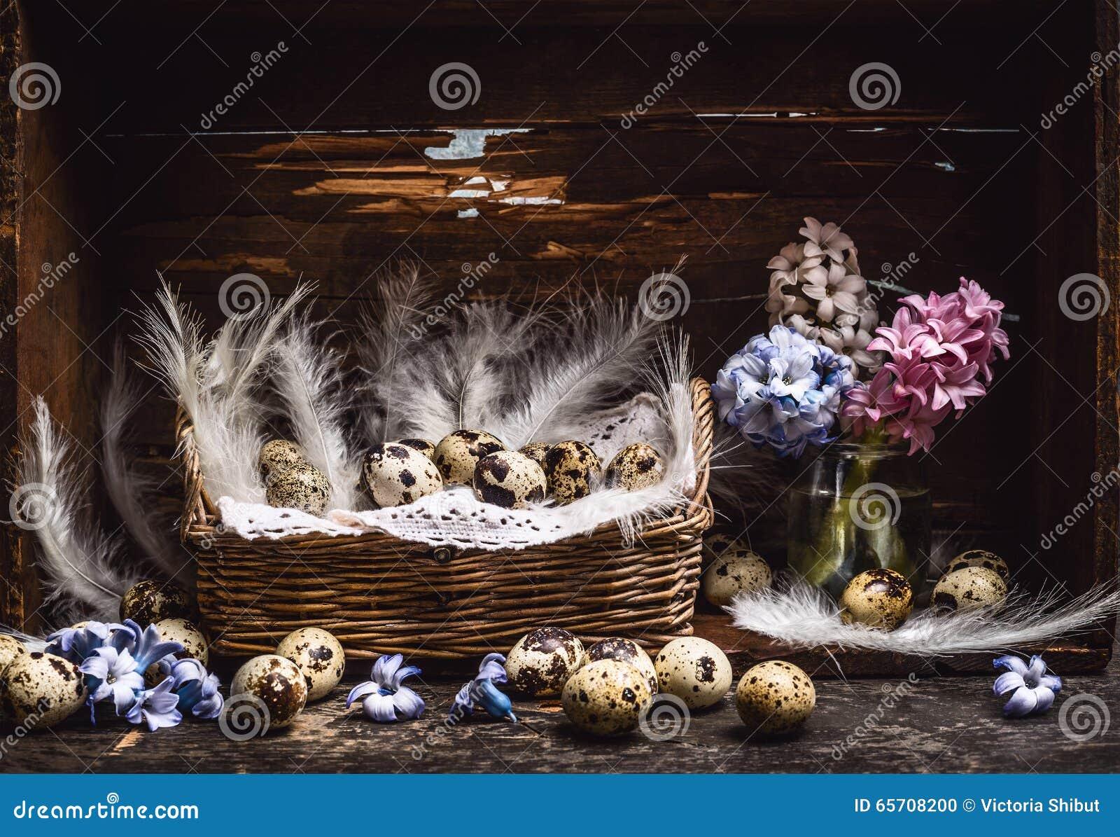 Korb mit Wachteleiern und Federn und Frühling blüht Hyazinthenbündel auf Weinleseholztisch, über rustikalem Hintergrund, Seitenan