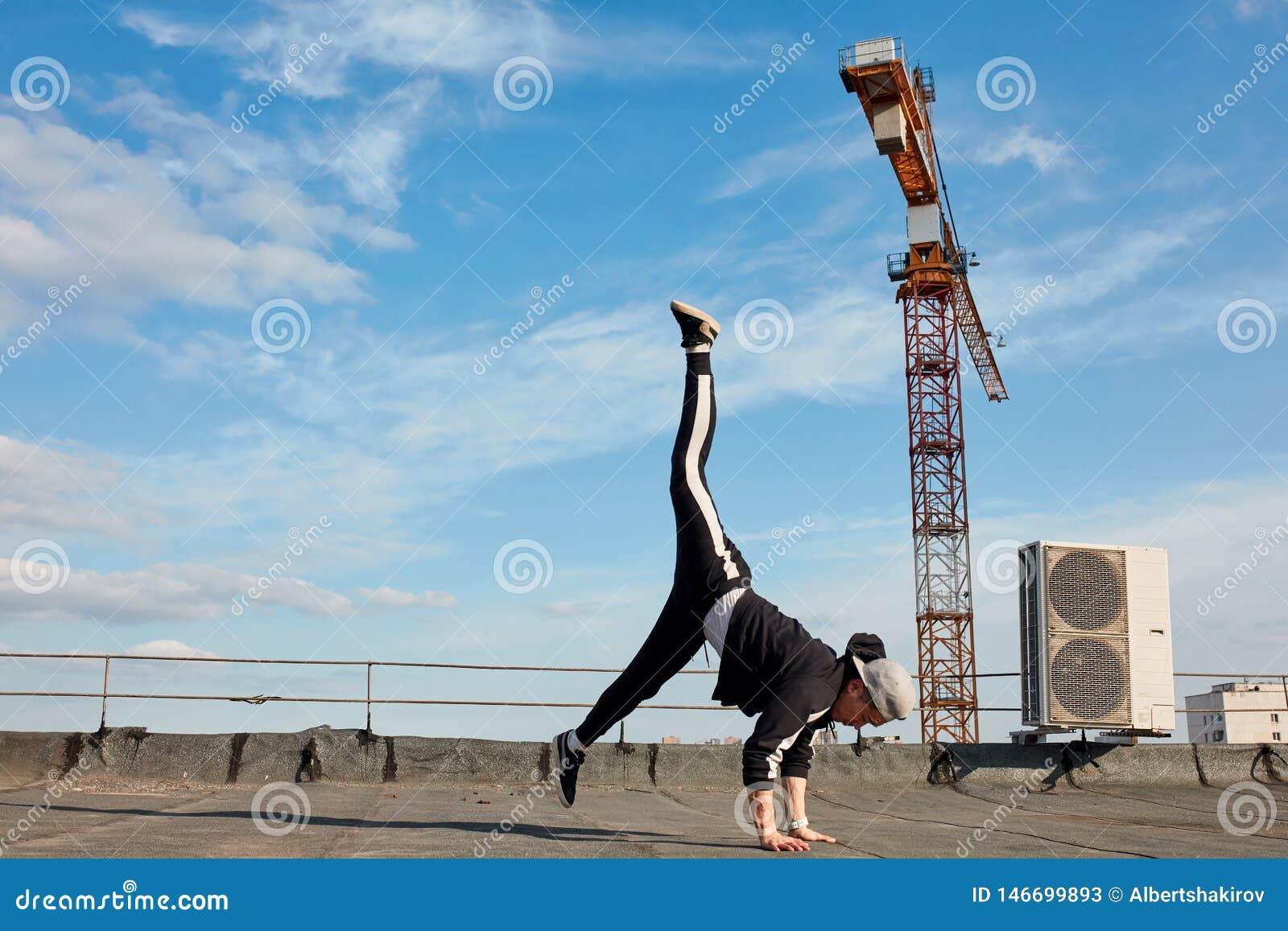 Koreański miastowy stylowy męski tancerza spełniania breakdance handstand na wierzchołka dachu