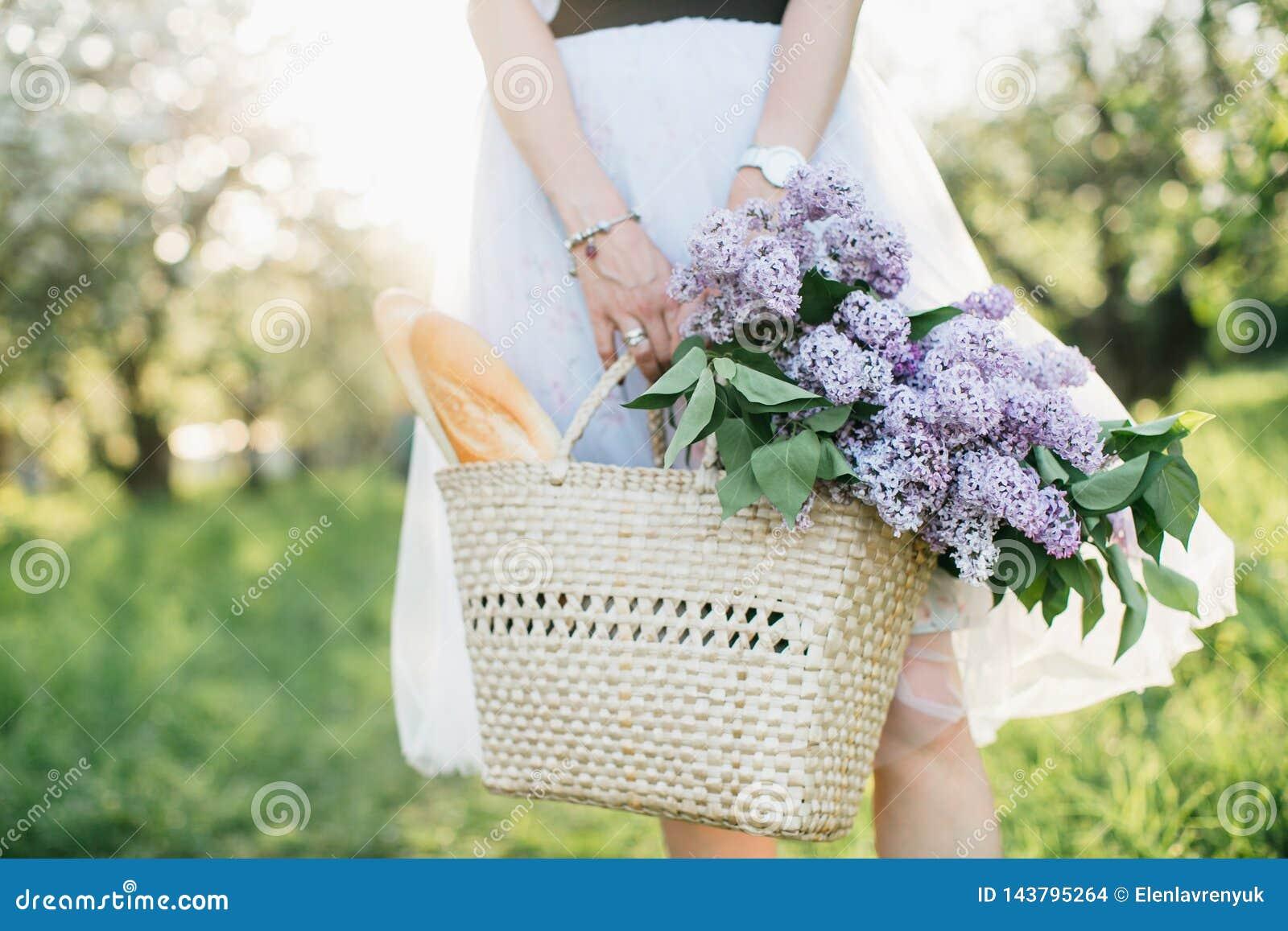 Korg med buketten av lilor och bagetten i kvinnahänder på bakgrund av naturen