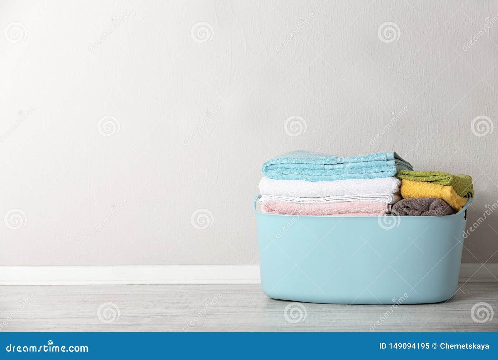 Korg med den rena tvätterit på golv nära färgväggen