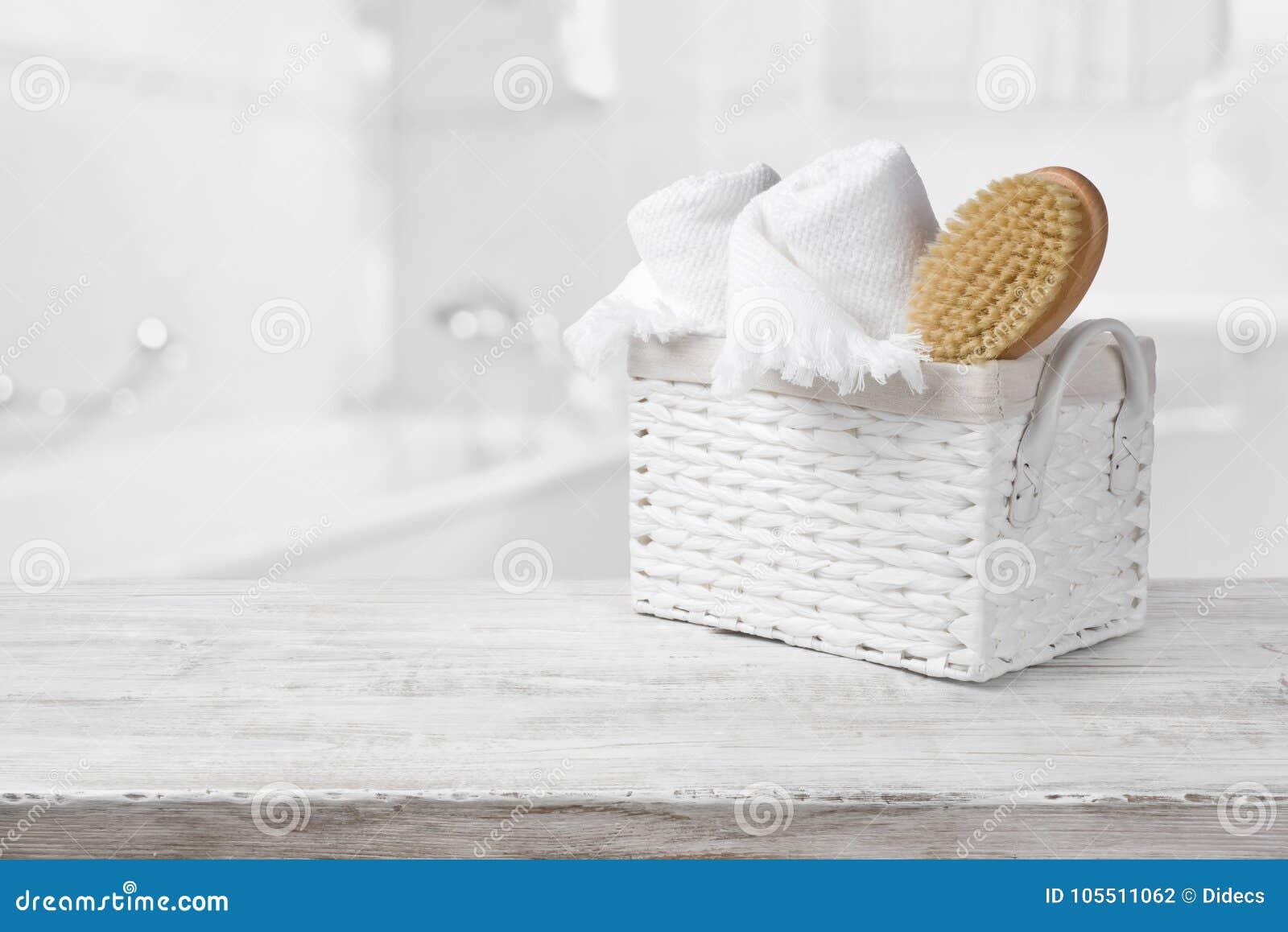 Korgen, handdukar och badet borstar på trä över suddigt badrum