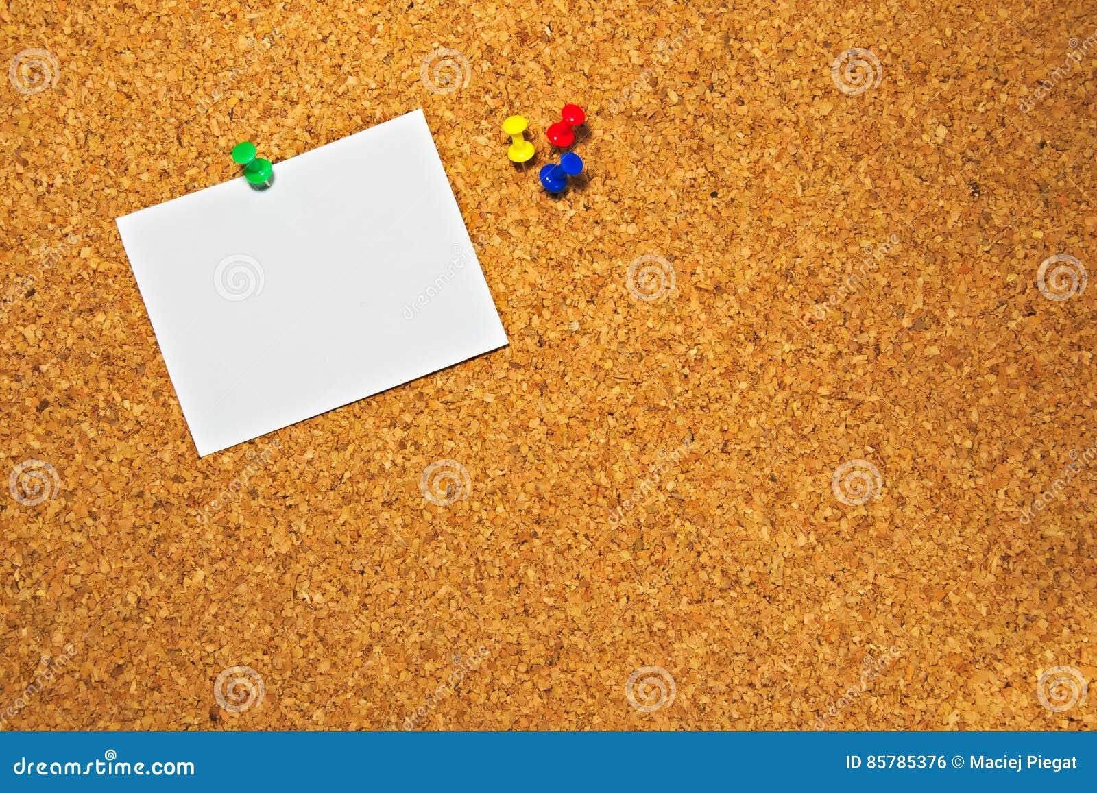 Korkbräde med ett tomt stycke av papper som är klart att skriva meddelanden